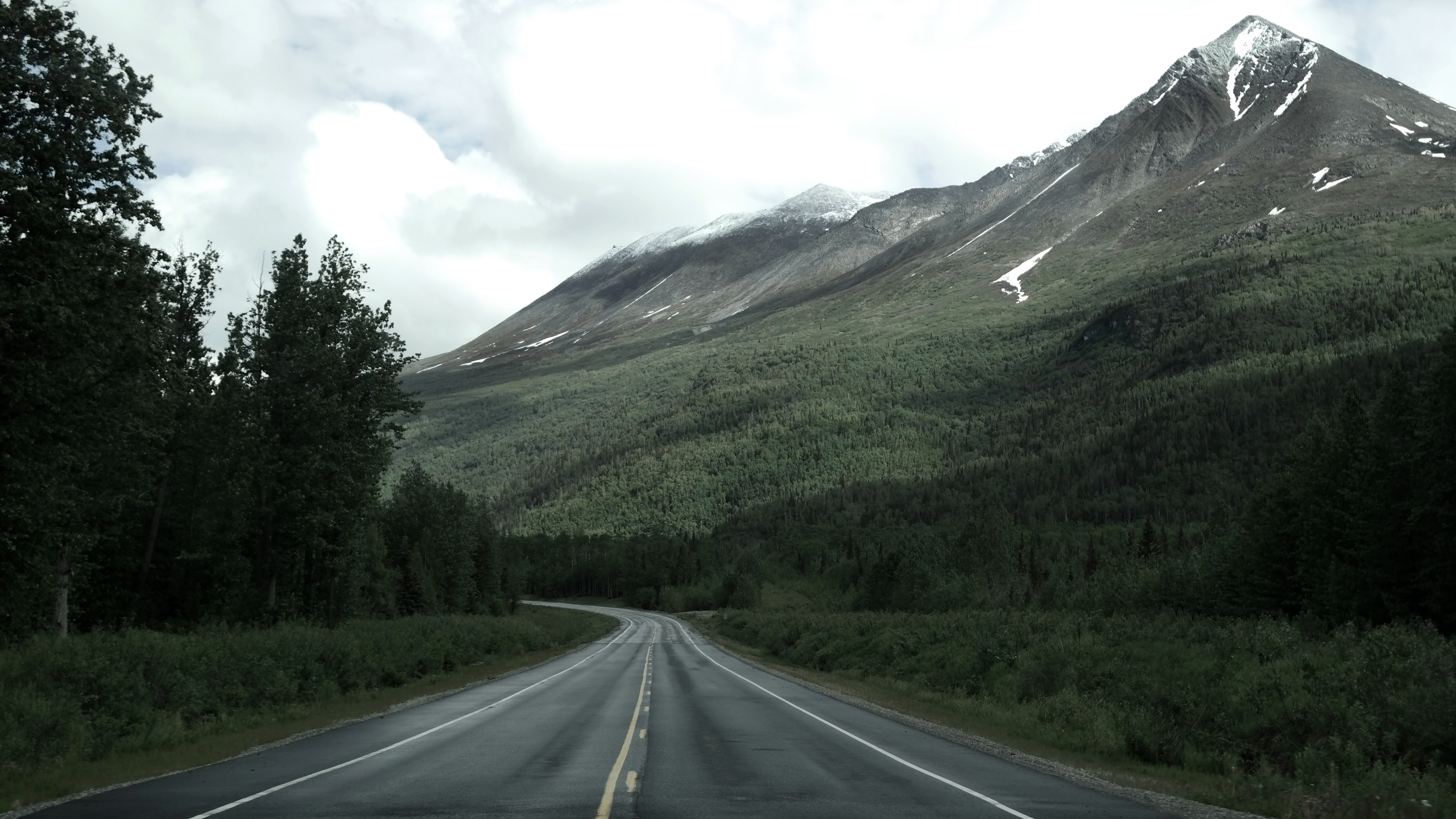 An empty asphalt road near a wooded slope of tall snow-capped mountains