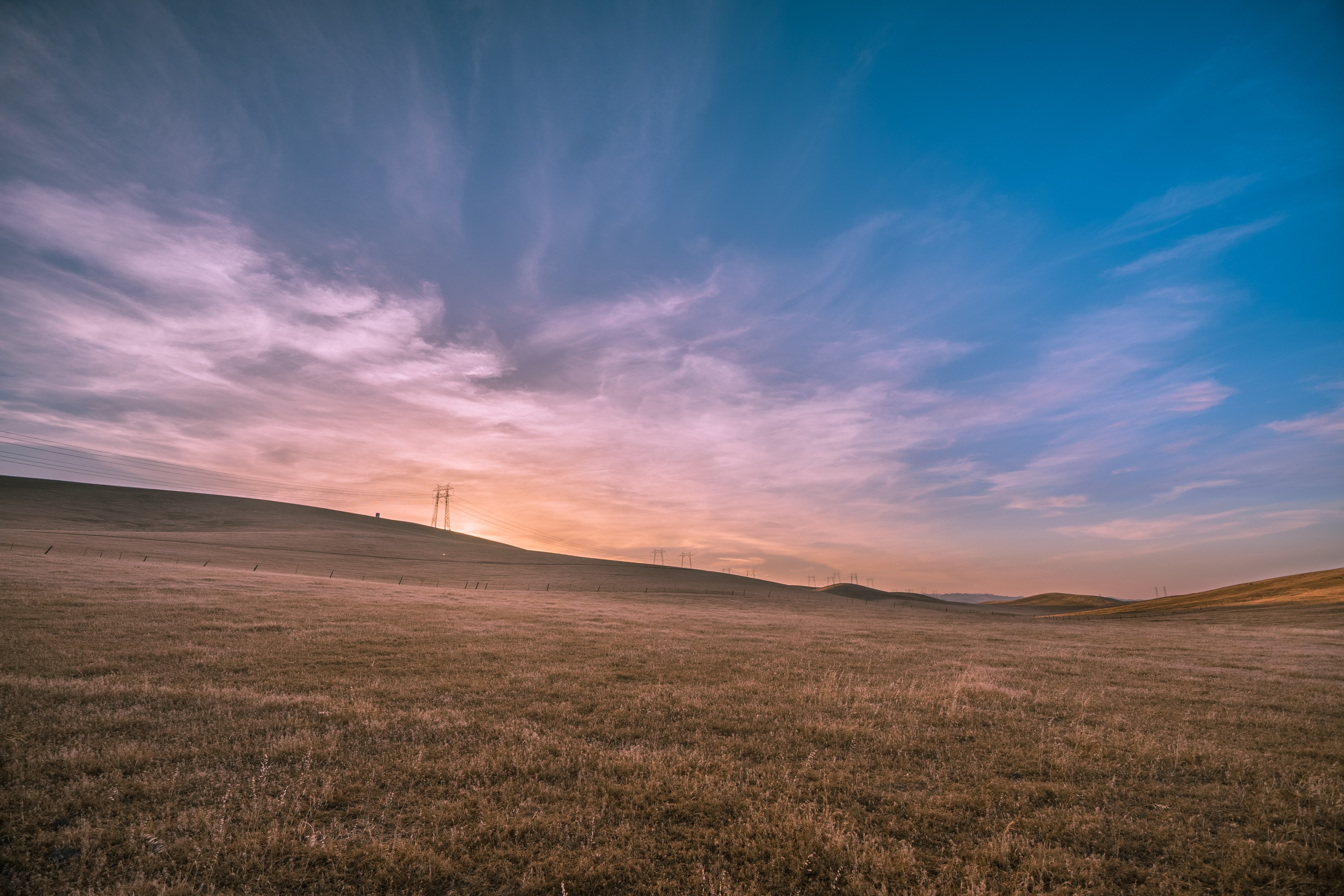 A countryside field during a pink and blue sunset