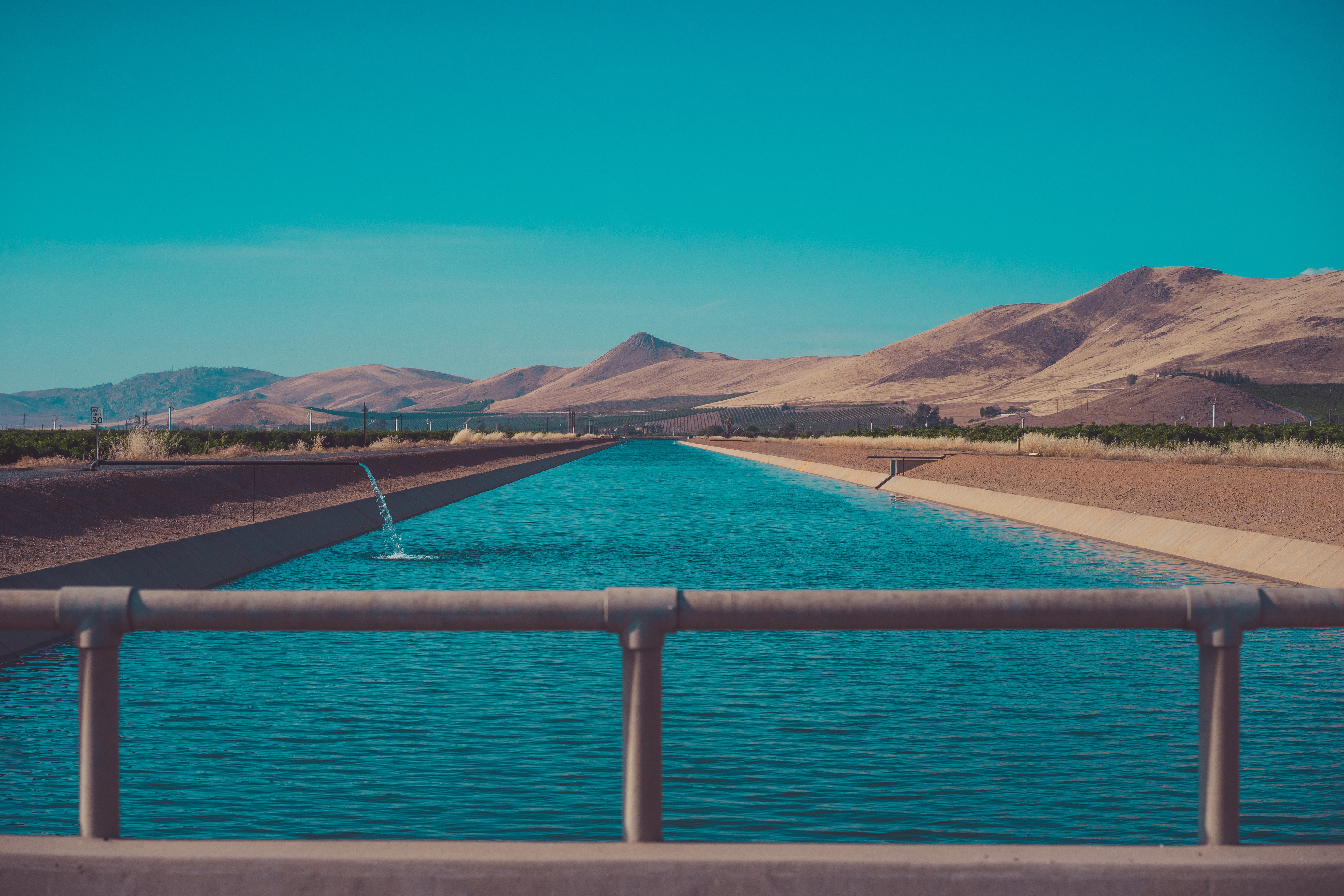 Canal bridge view of a blue water reservoir in the desert