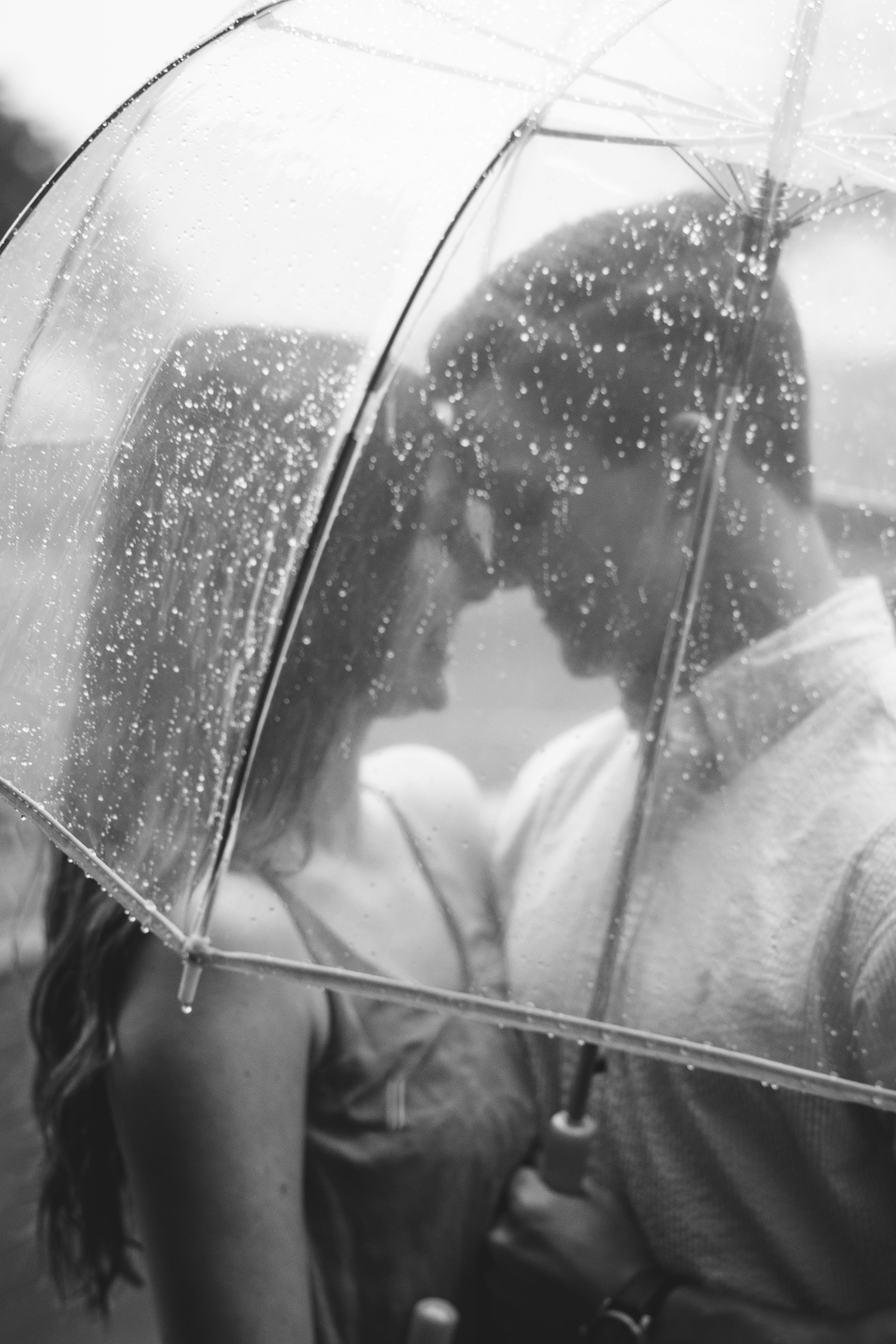 Couple stands close together under transparent umbrella in the rain