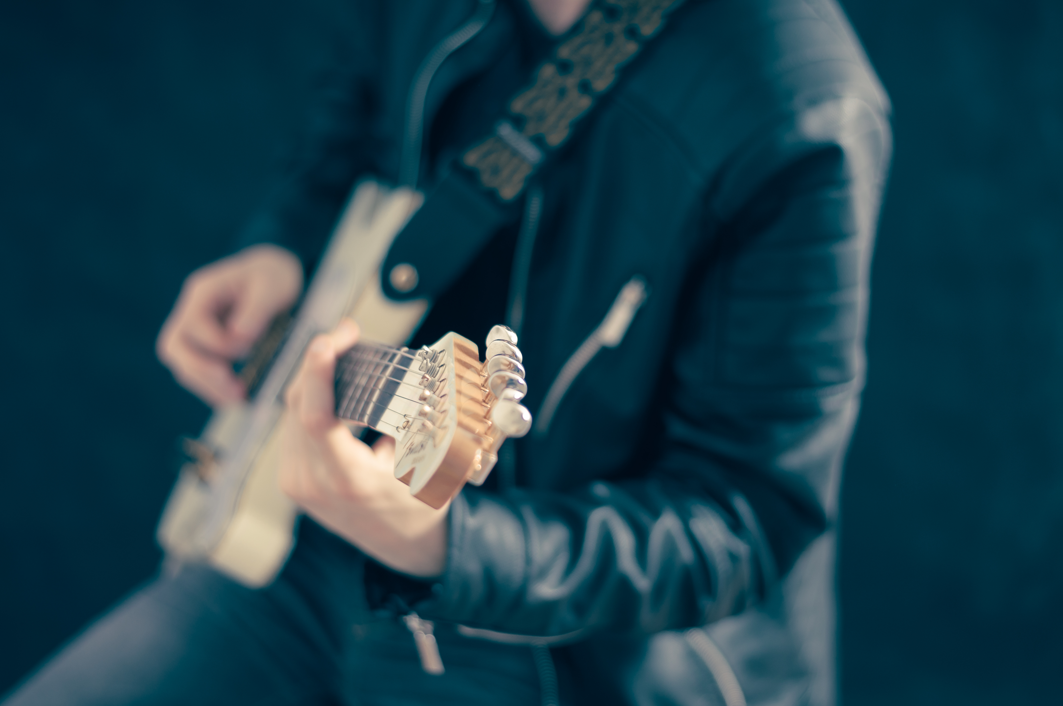 A blurry shot of a person in a leather jacket playing the guitar
