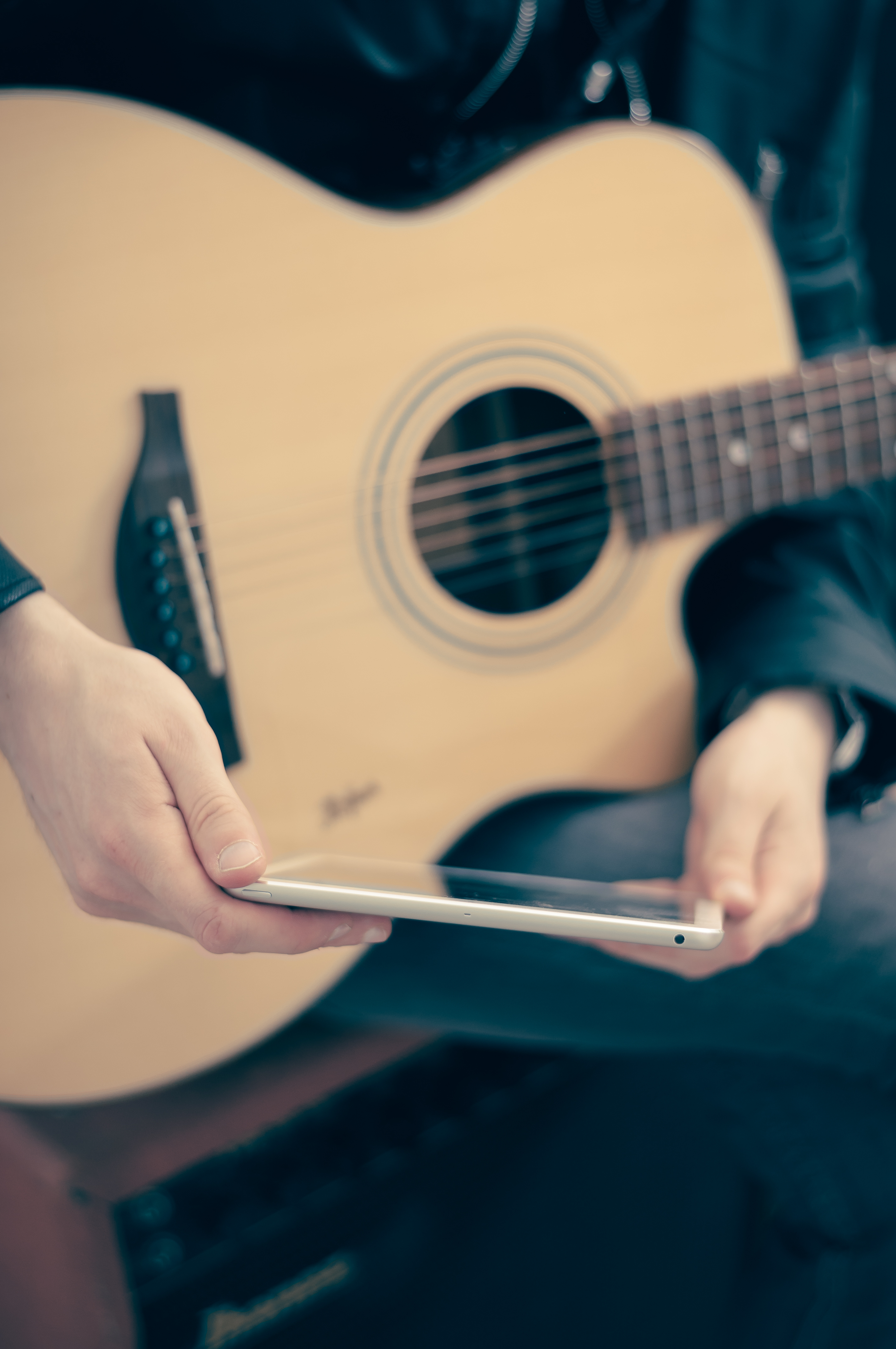 person with guitar on lap holding tablet