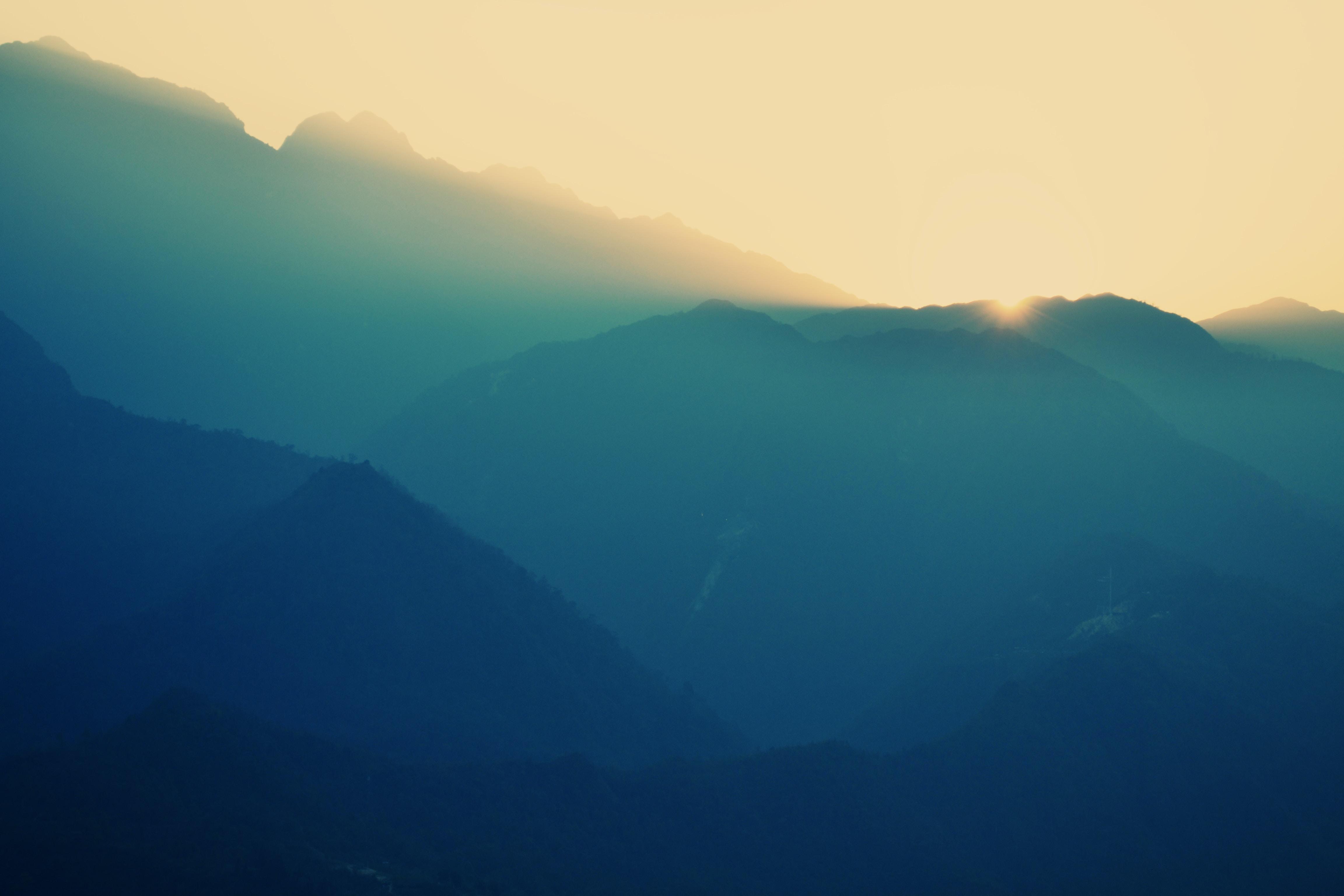 A hazy shot of high mountain ridges during sunset