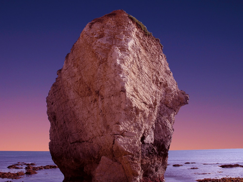 brown rock formation with body of water