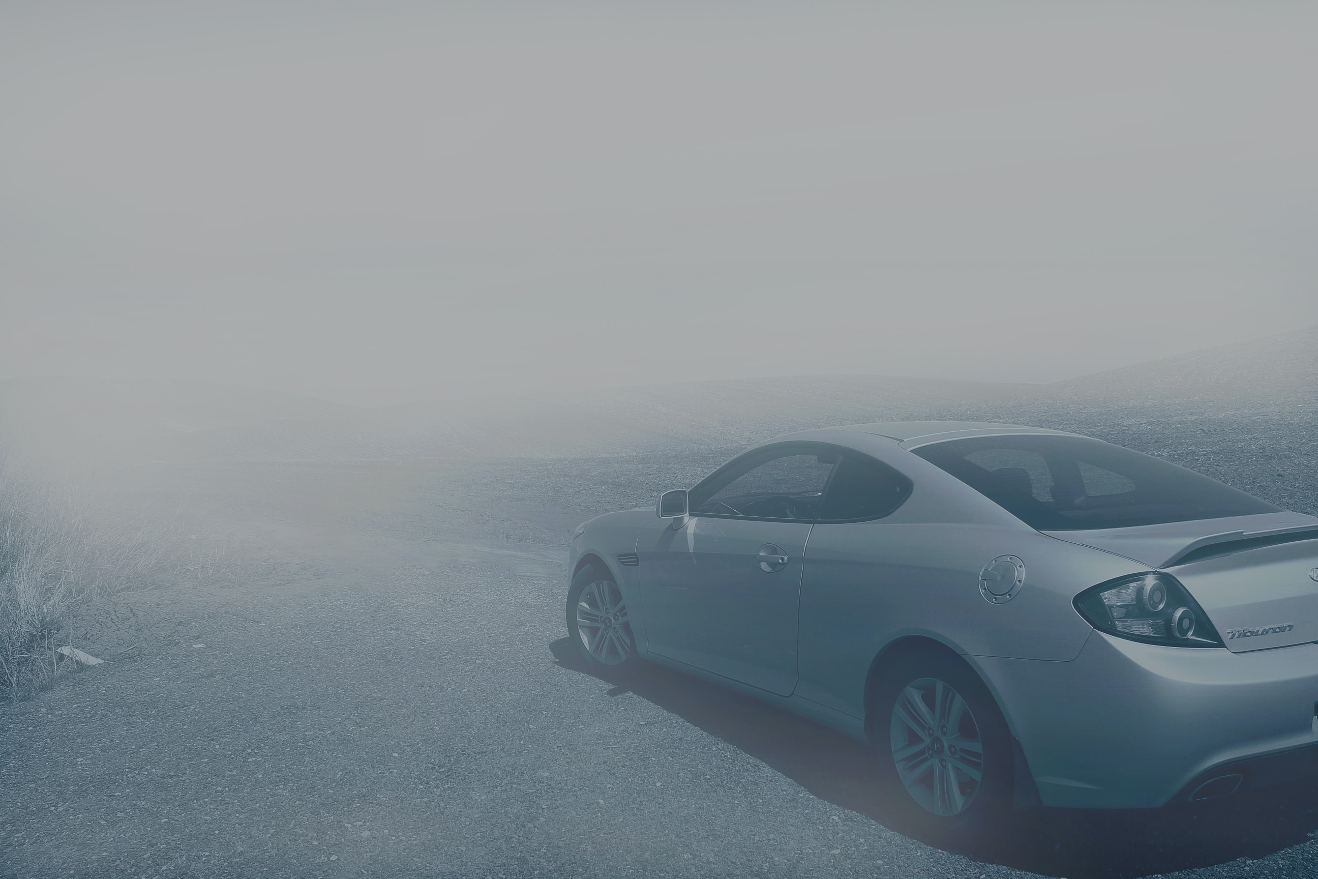 A sports car surrounded by fog in a barren landscape