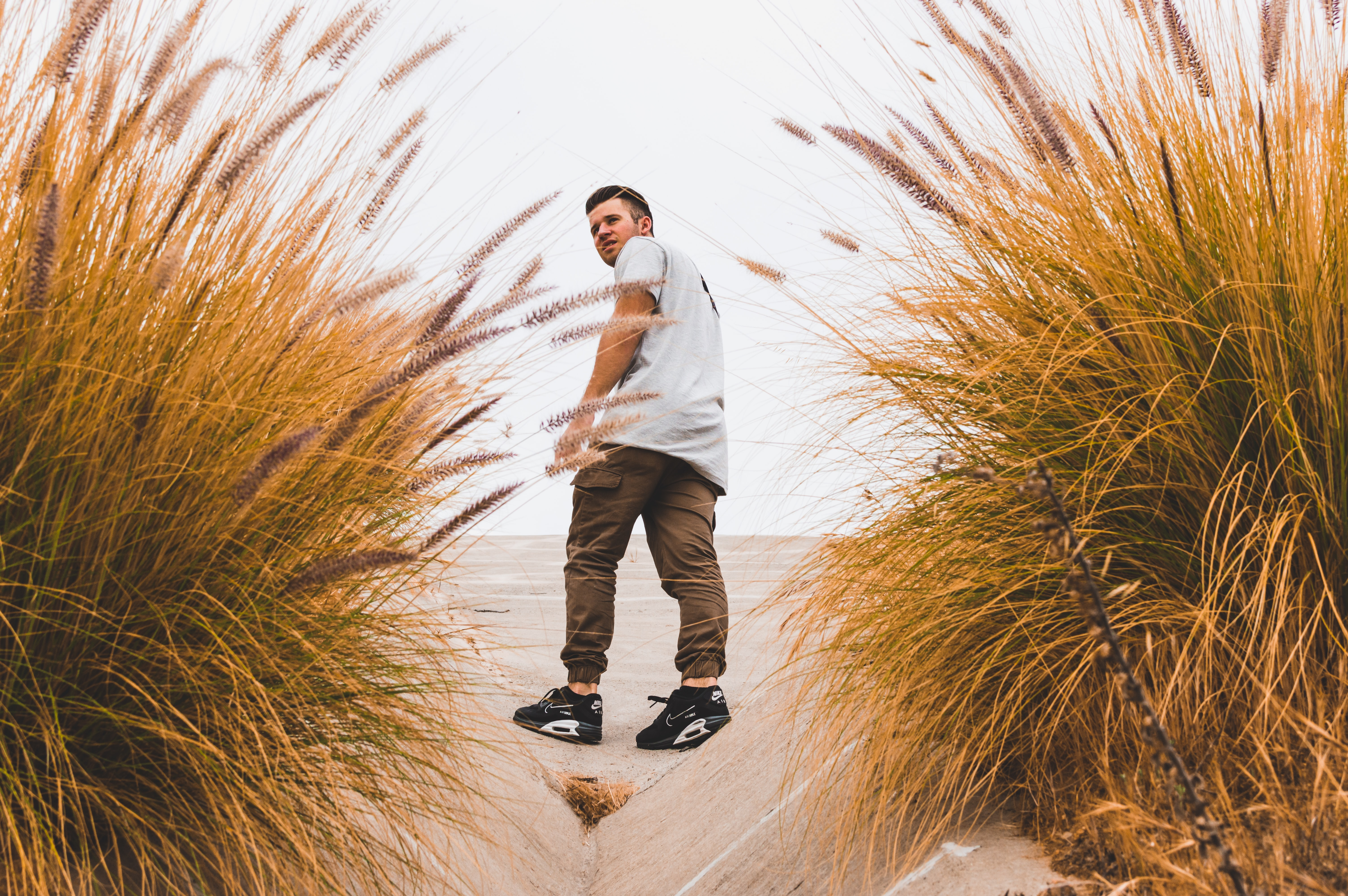 man looking back on tall brown grass