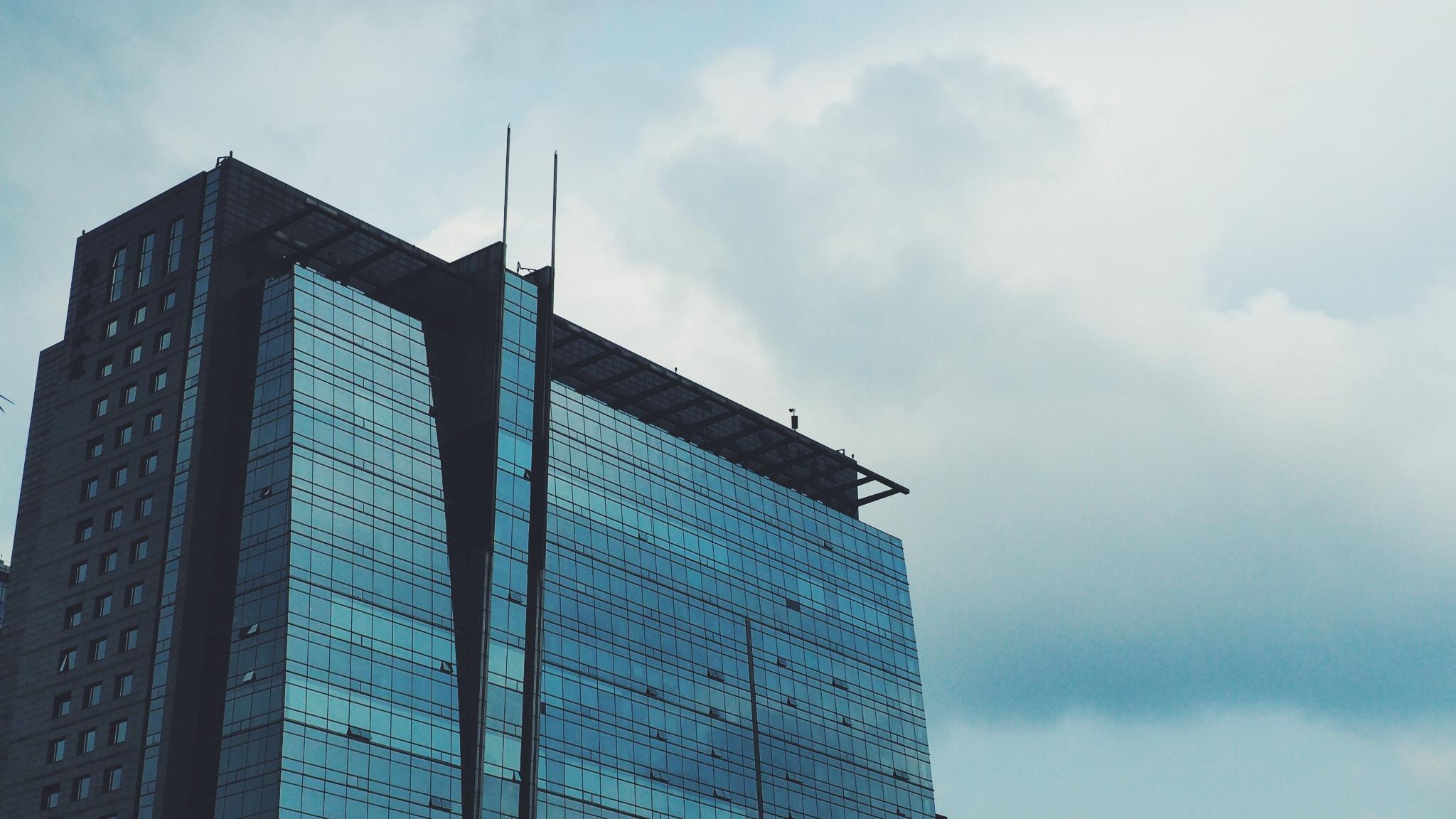 The modern glass facade of an office building under cloudy sky