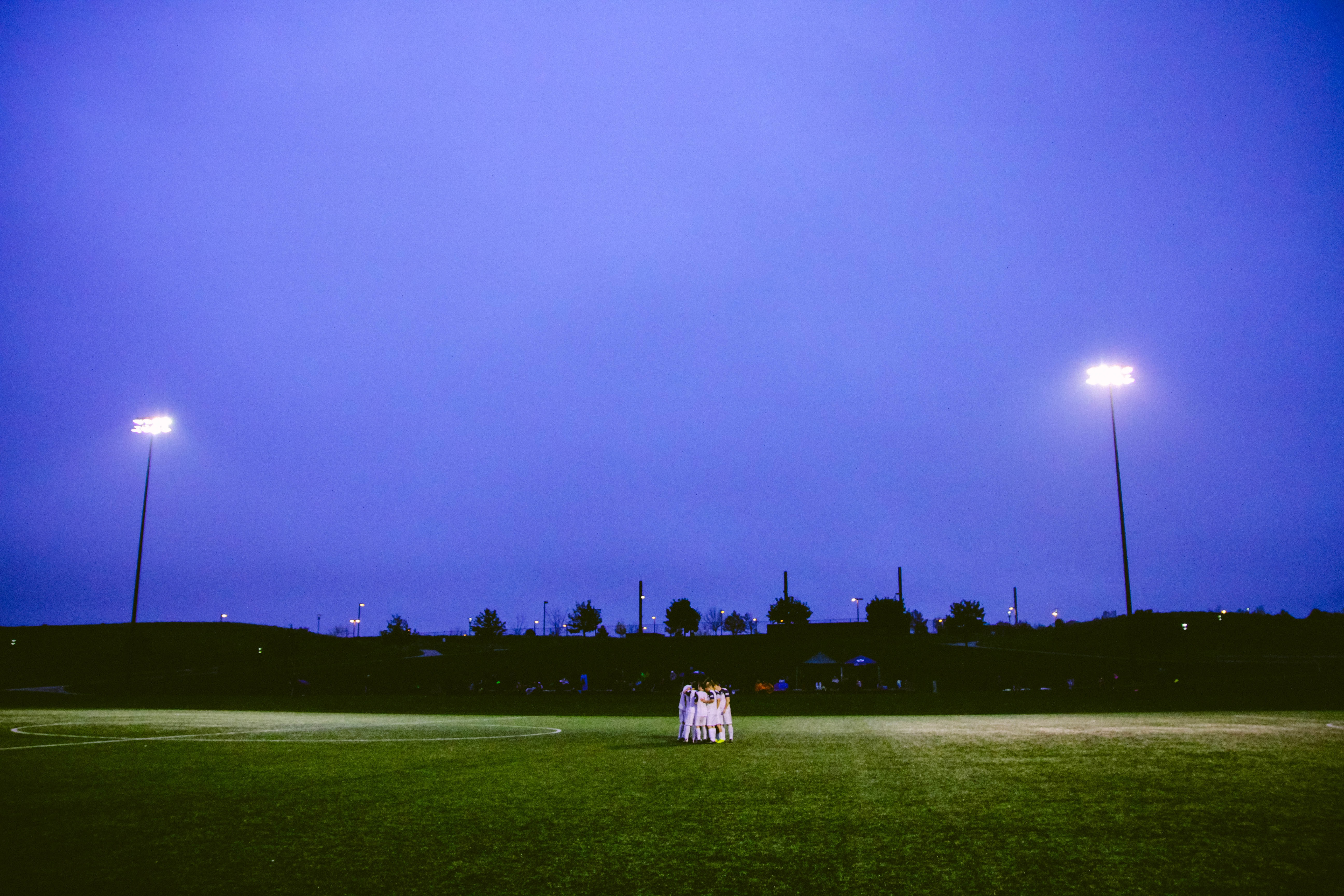 A grass football field in the middle of the evening