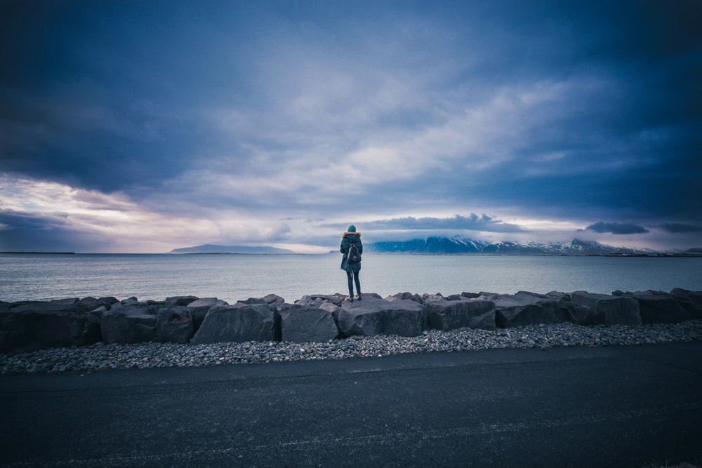 photo of person standing on rock looking sea during daytime