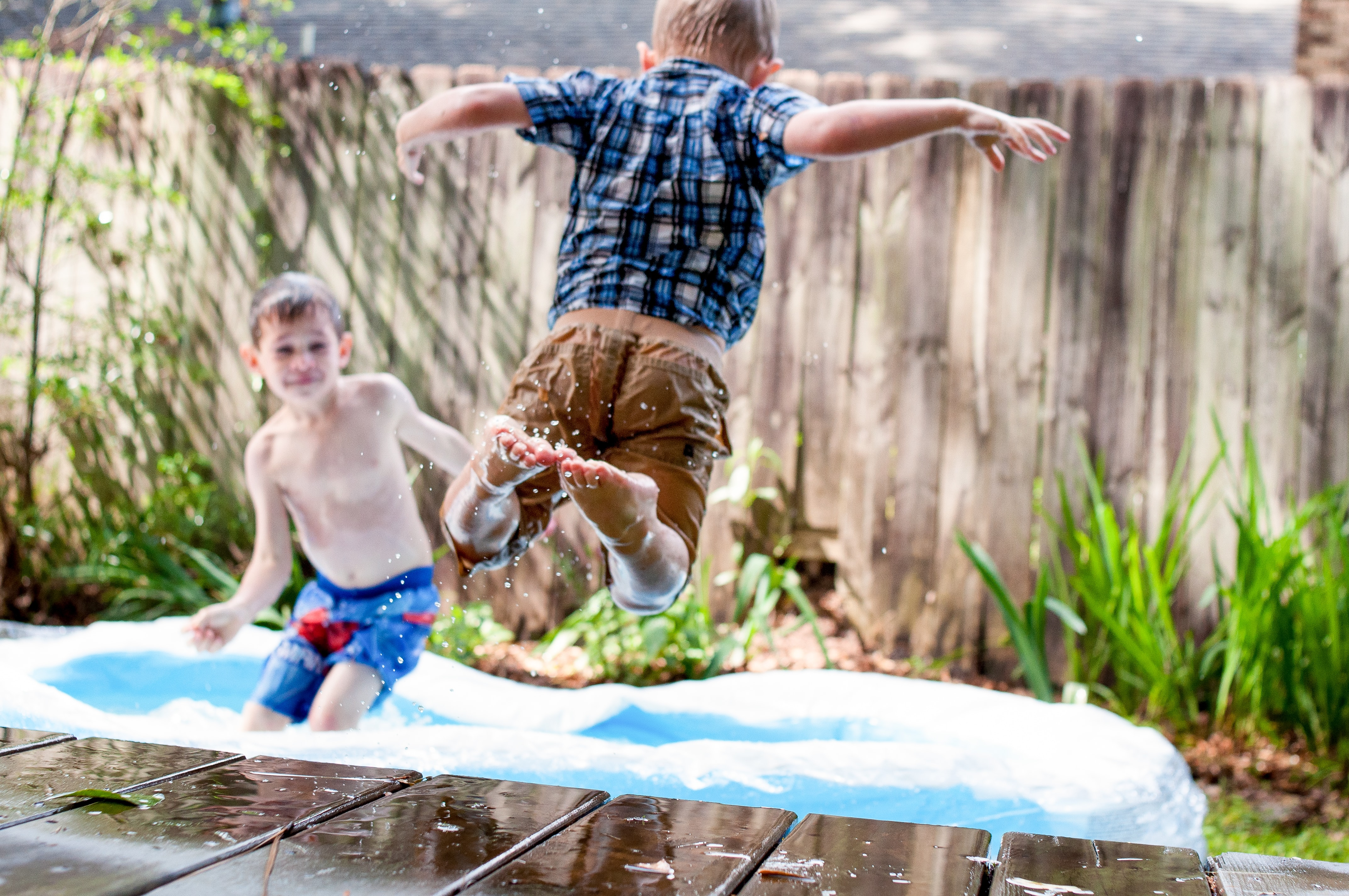 two boys playing in inflatable pool during daytime