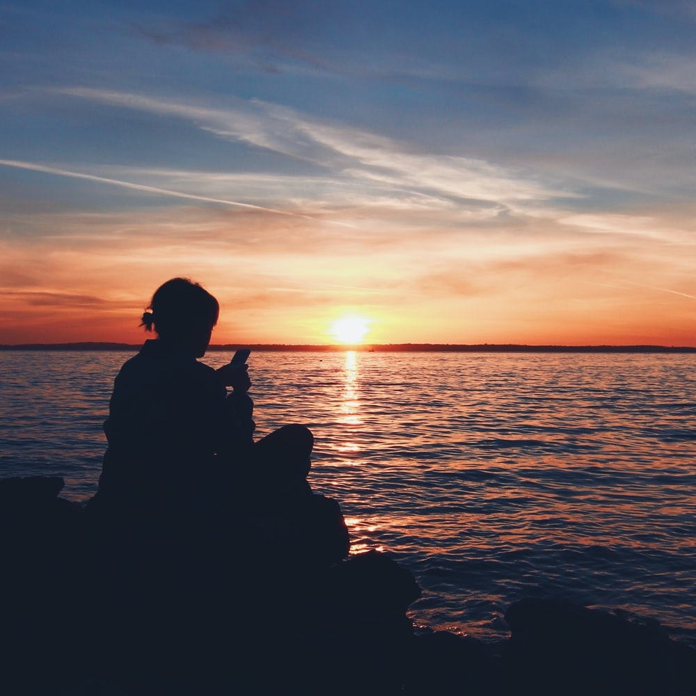 silhouette photo of person sitting on boulder near body of water