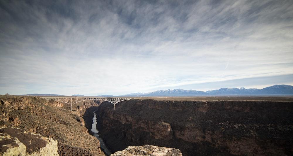 white bridge in between rock mountain