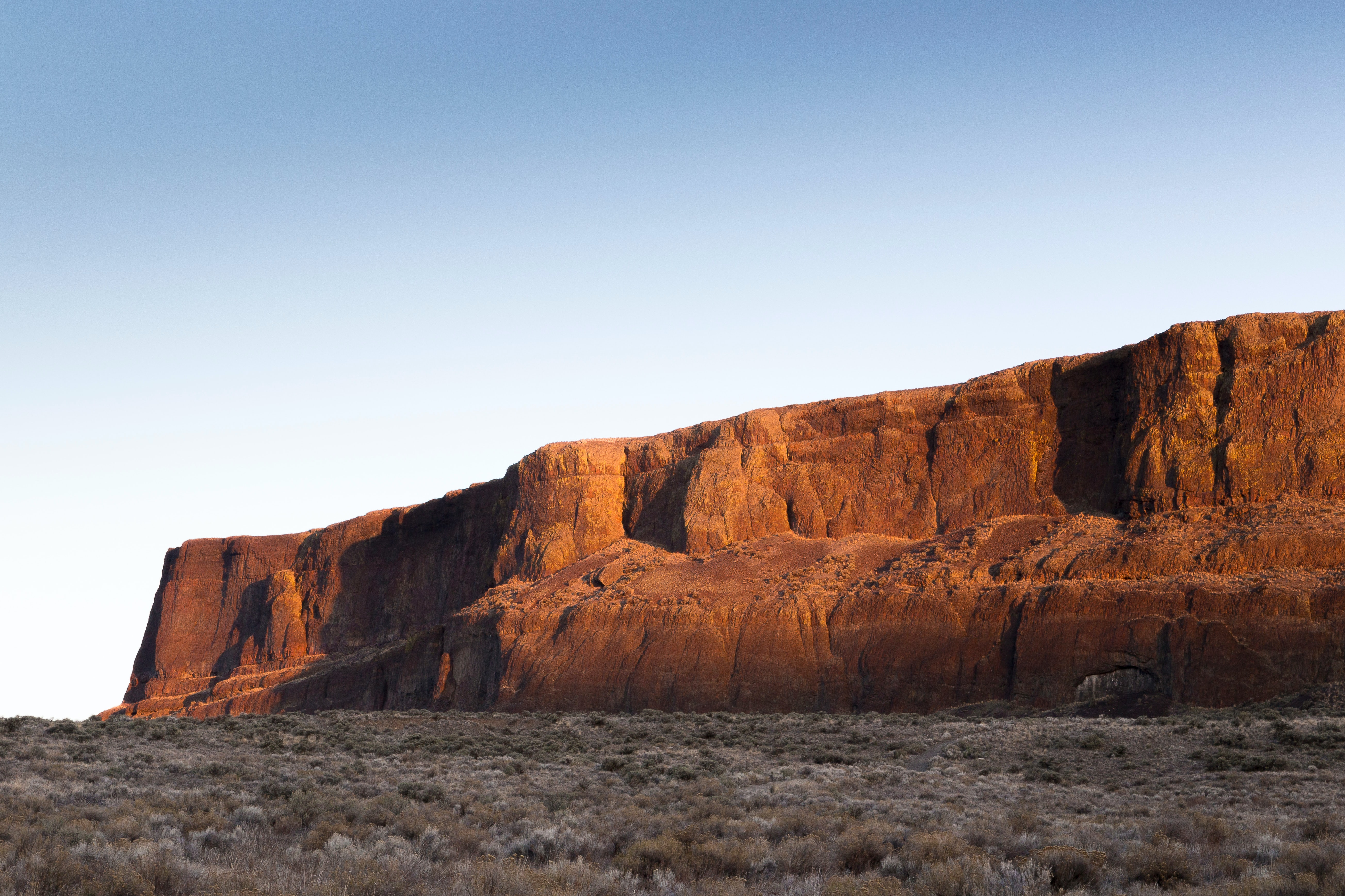 A large sandstone formation in the middle of arid grassland