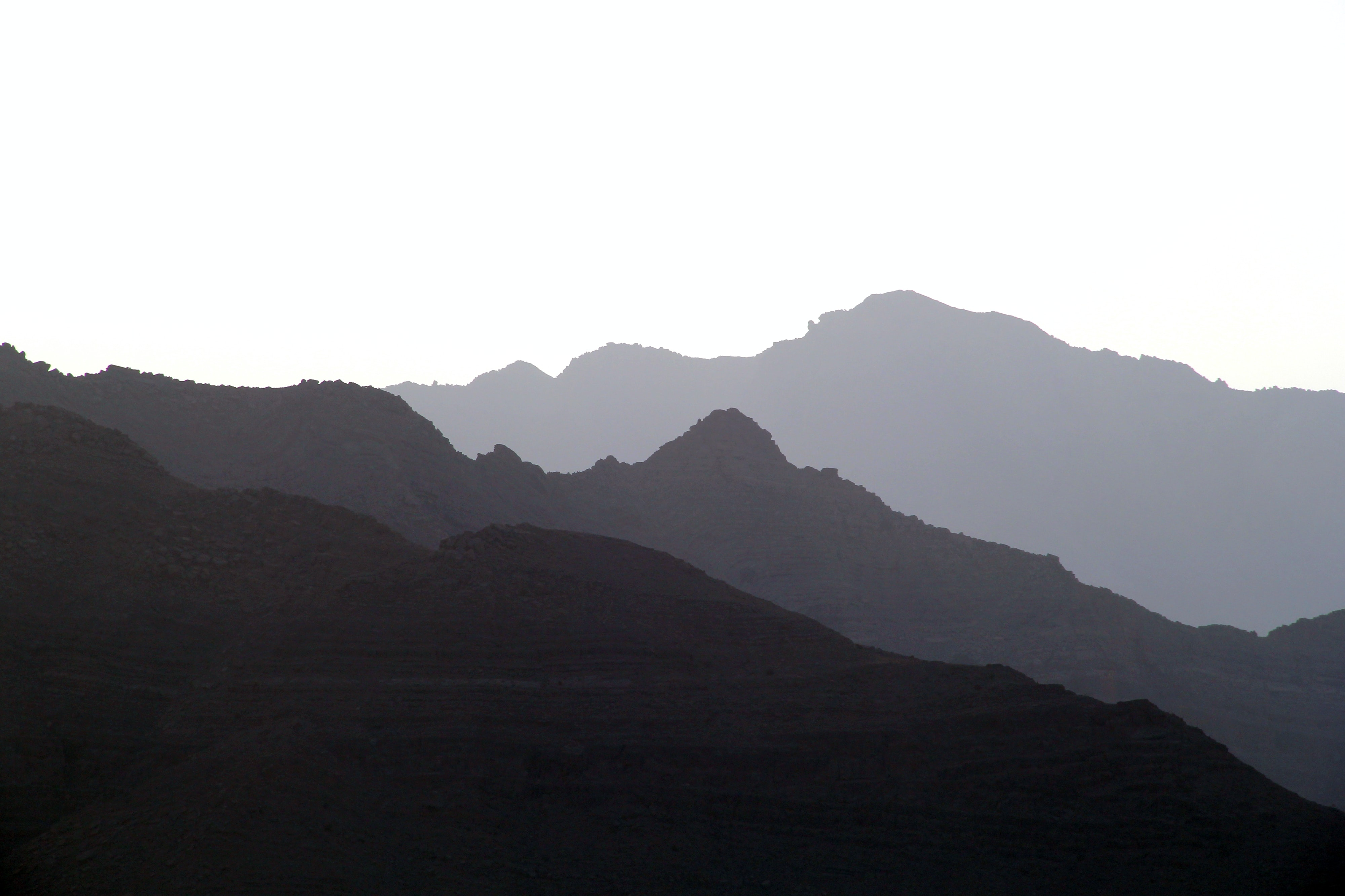 Dark silhouettes of rocky mountain ridges under a pale white sky