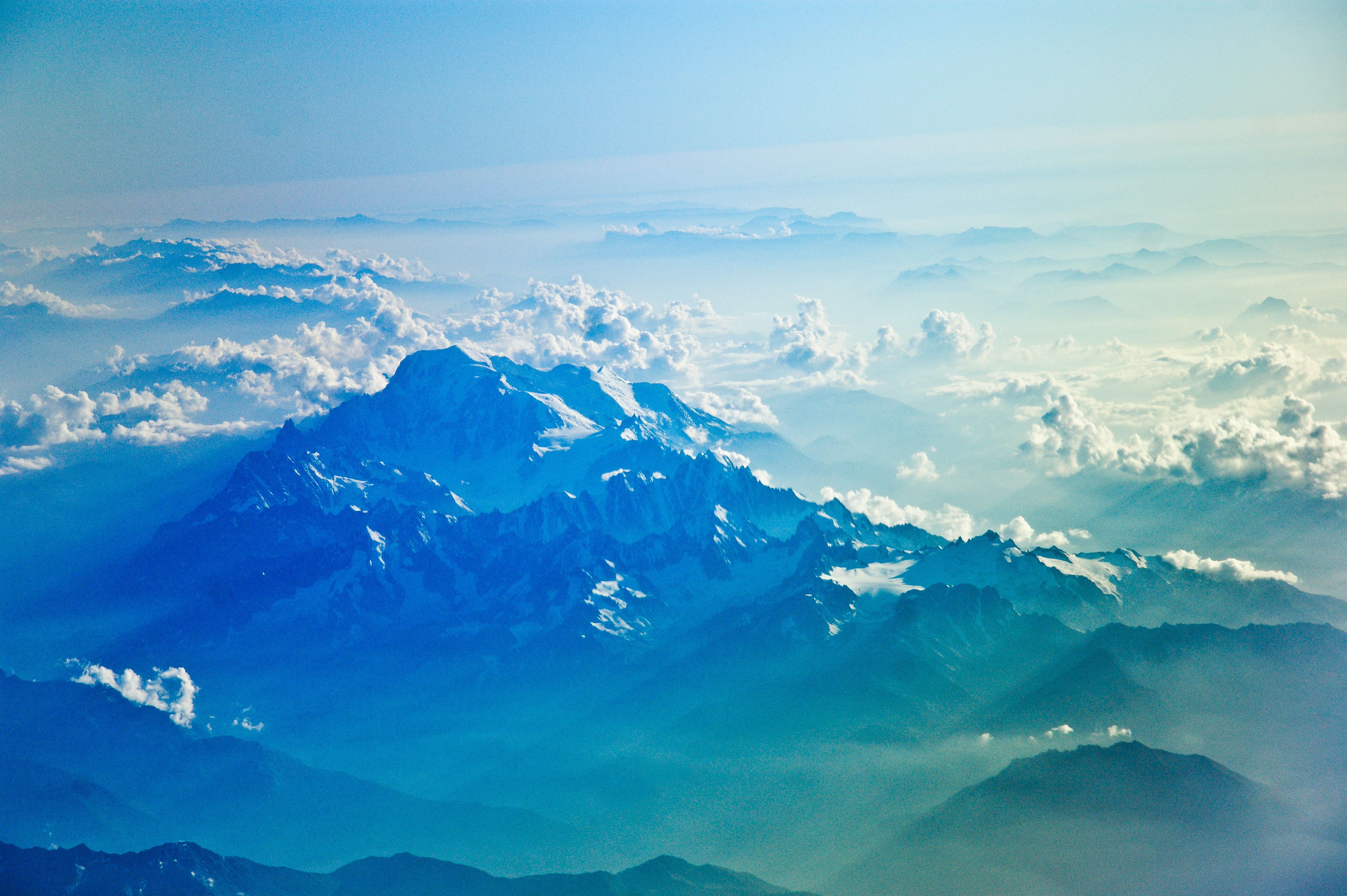 A bird's-eye view on a snow-capped mountain range with clouds obscuring the horizon