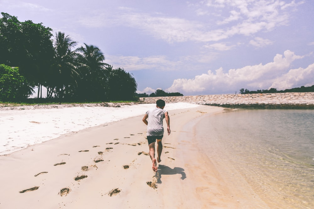 man wearing white t-shirt running in the sand