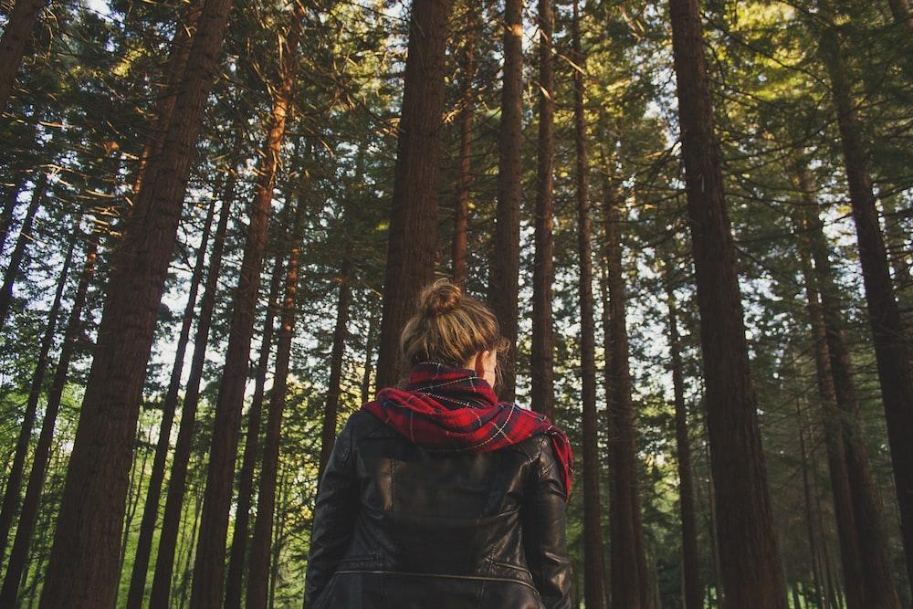 woman wearing black jacket looking at trees