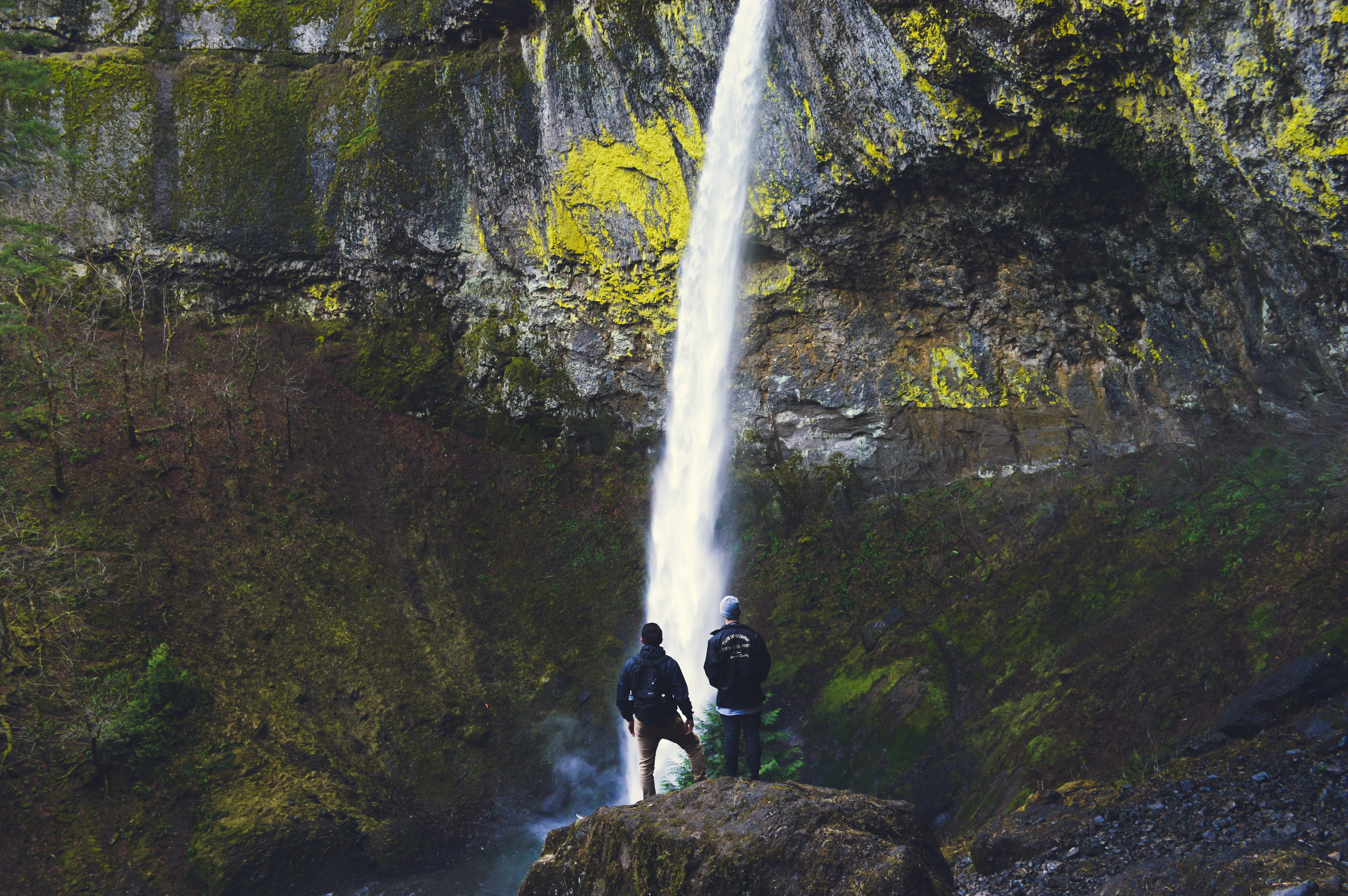 Two male hikers looking at a tall waterfall tumbling down from the rocky face