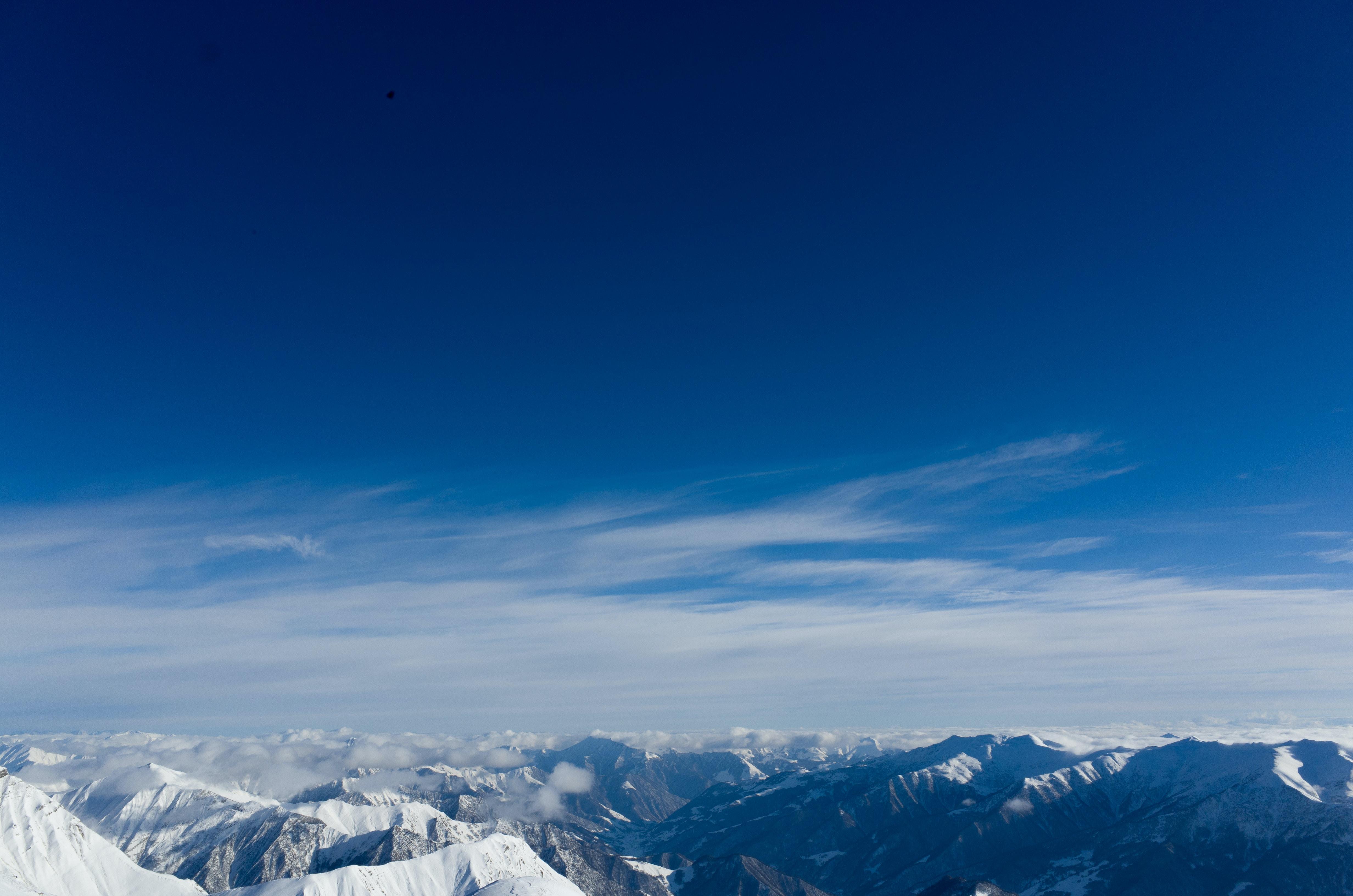 A dramatic mountainous landscape under a blue sky