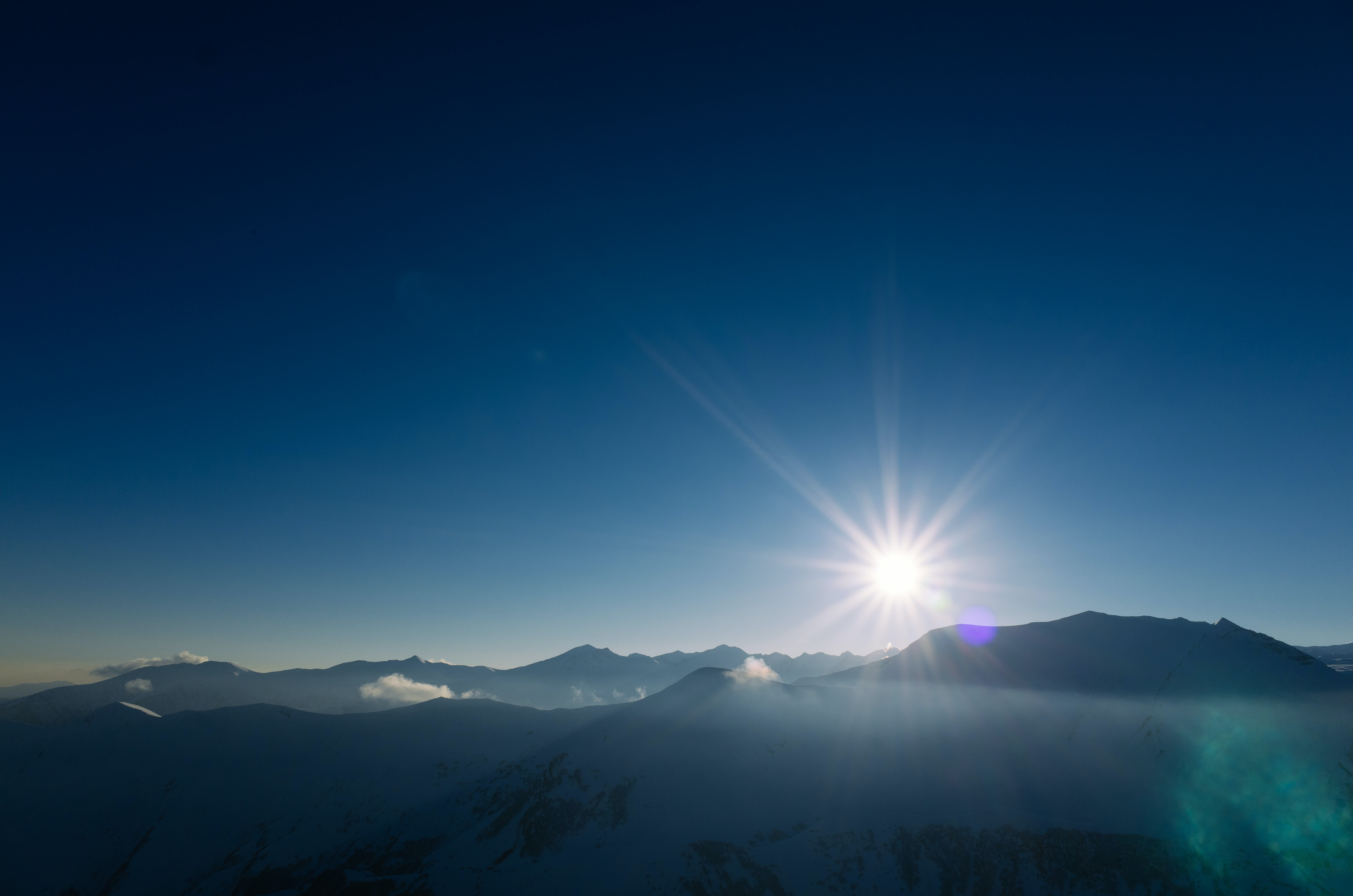 Sun rising above the silhouette of a mountain range