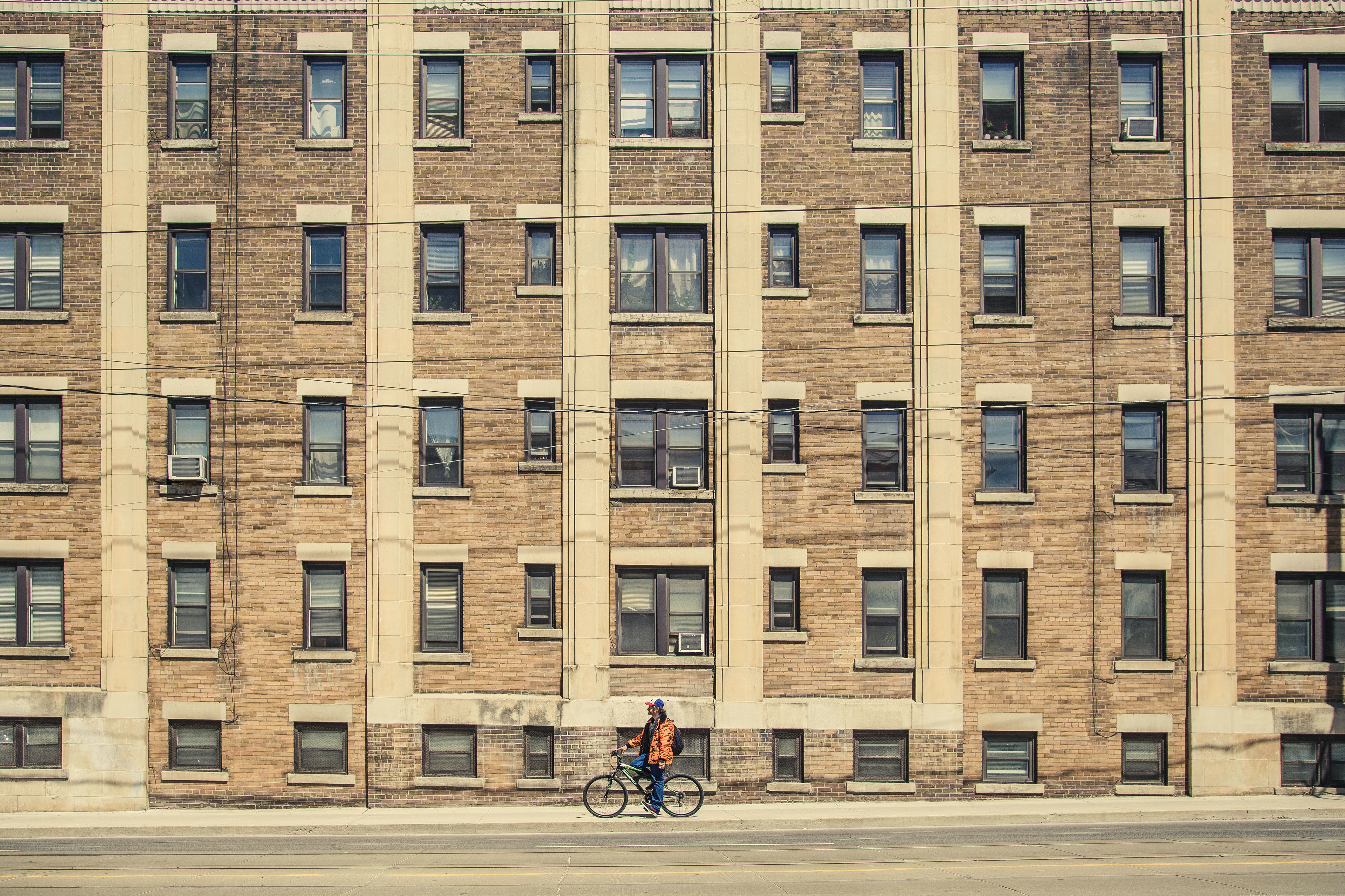Man in orange coat resting on bike in front of brown urban apartment building with windows