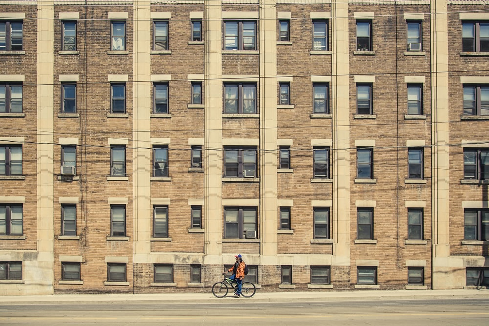 person riding bicycle near brown building