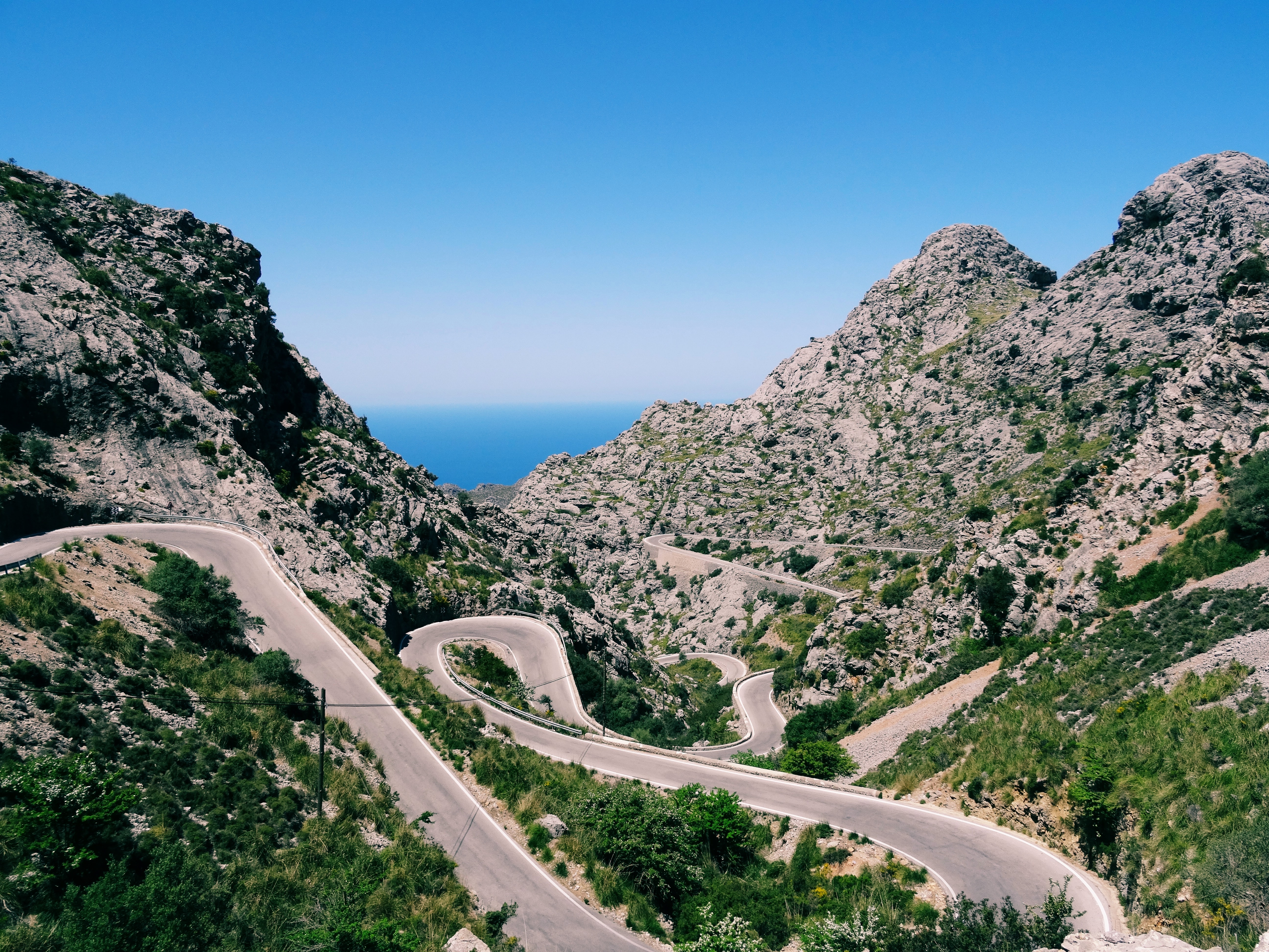 A narrow road twisting along the slopes of shrub-covered mountains
