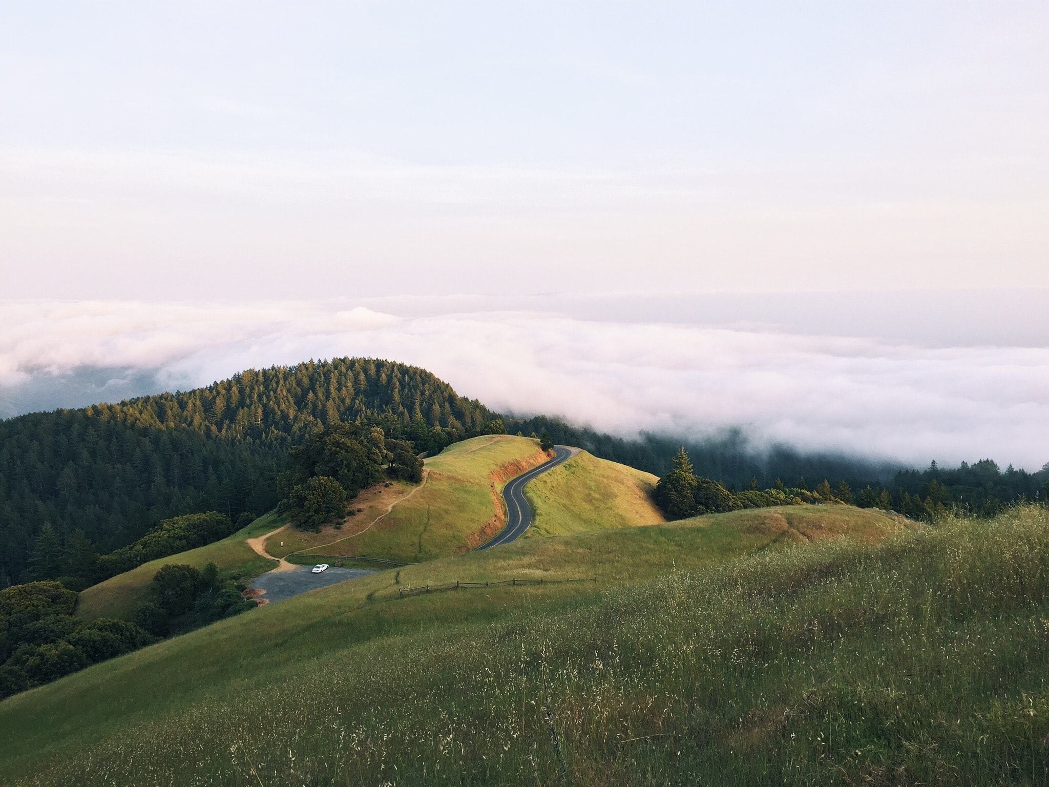A winding road through a green grassy valley surrounded by trees
