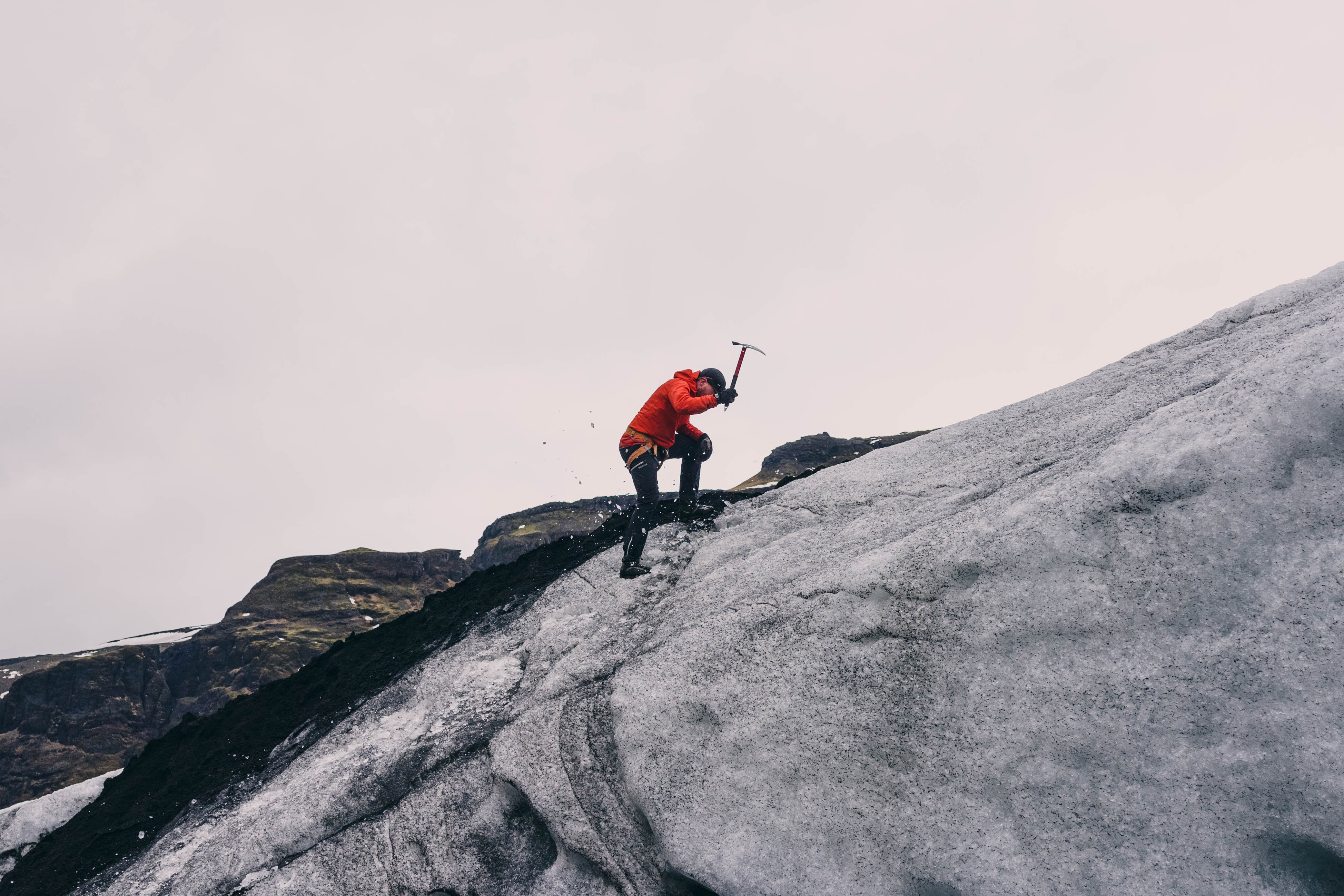 A man wearing a red jacket, holding an ice pick, ice climbing up a mountain