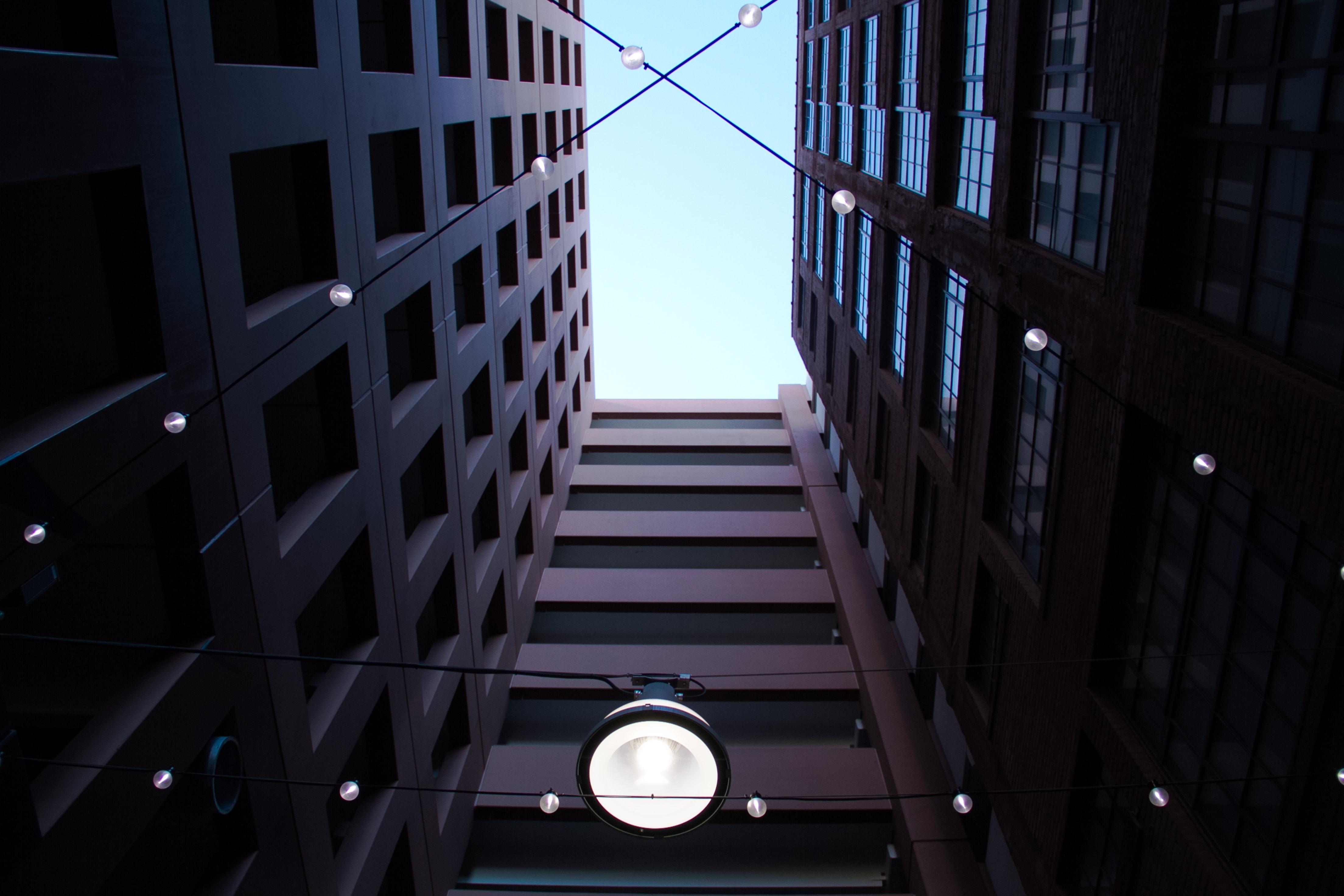 An upward photograph of an urban building and lights