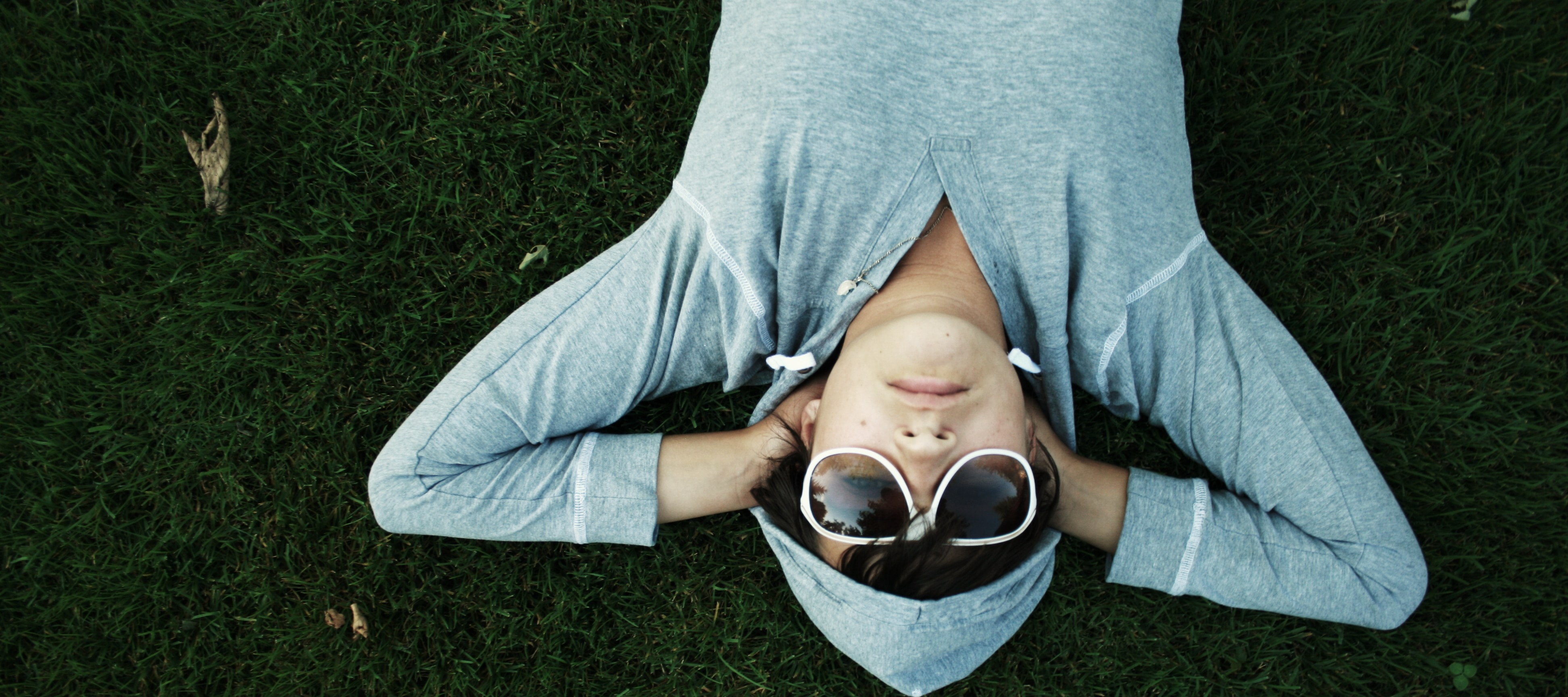 A person in dark glasses and a gray hoodie lying relaxed on green grass