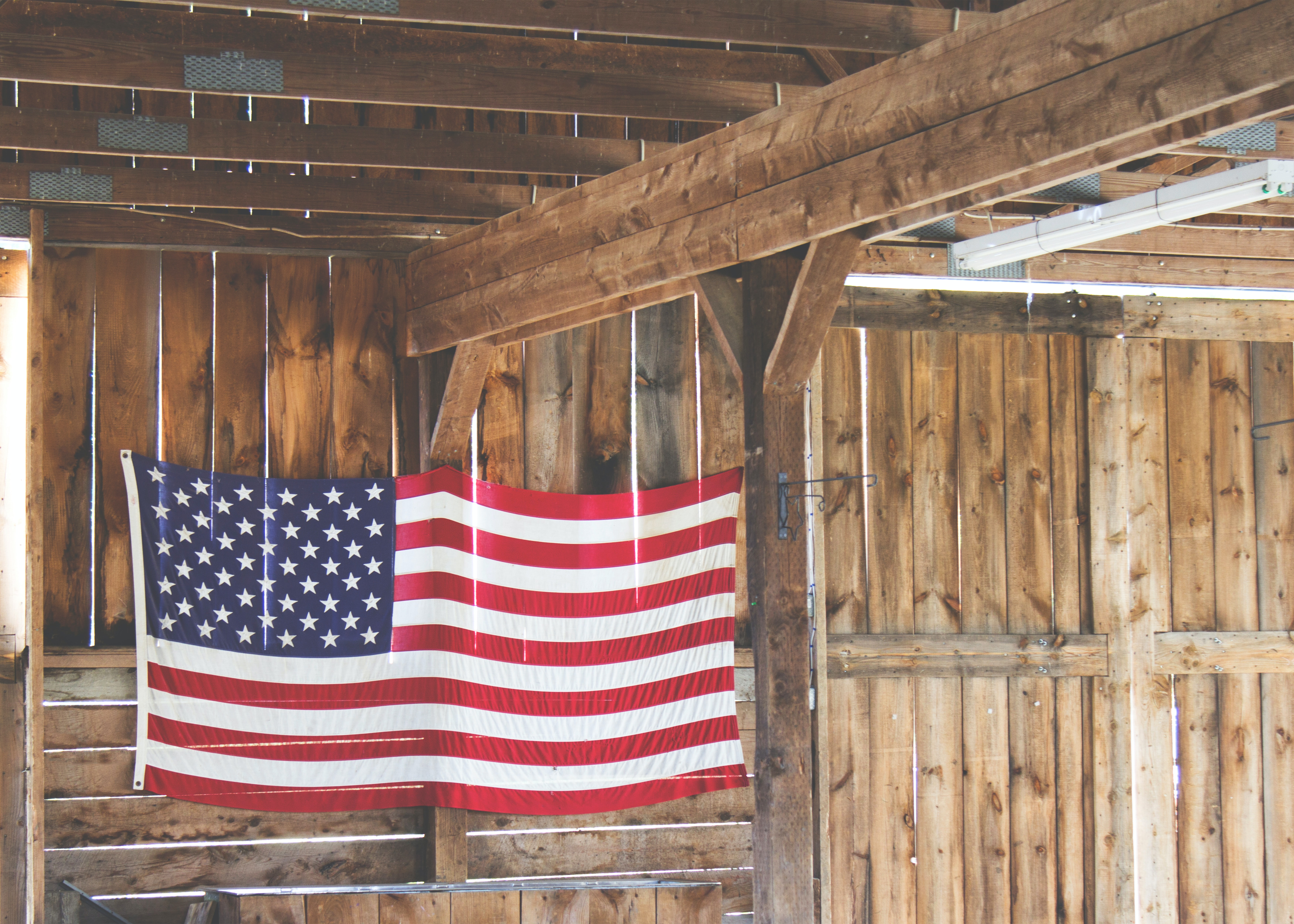 An American flag hanging in a wooden barn