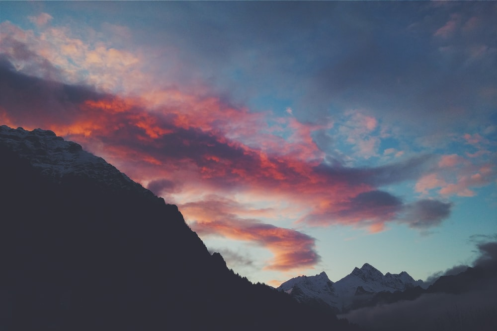 snow capped mountain under red clouds and blue sky