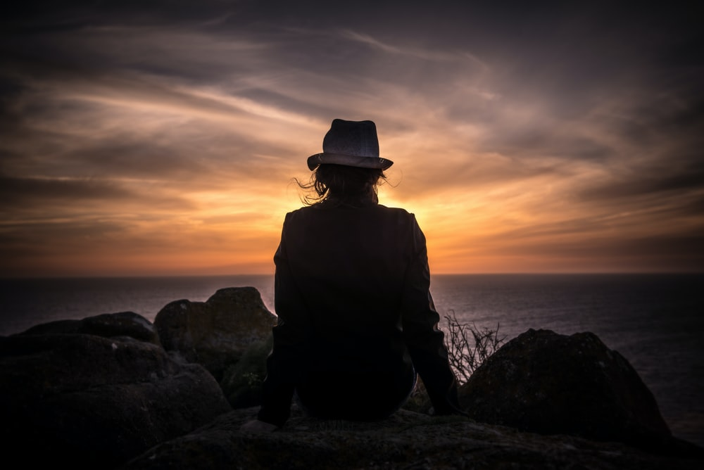silhouette of man sitting on stone looking at body of water