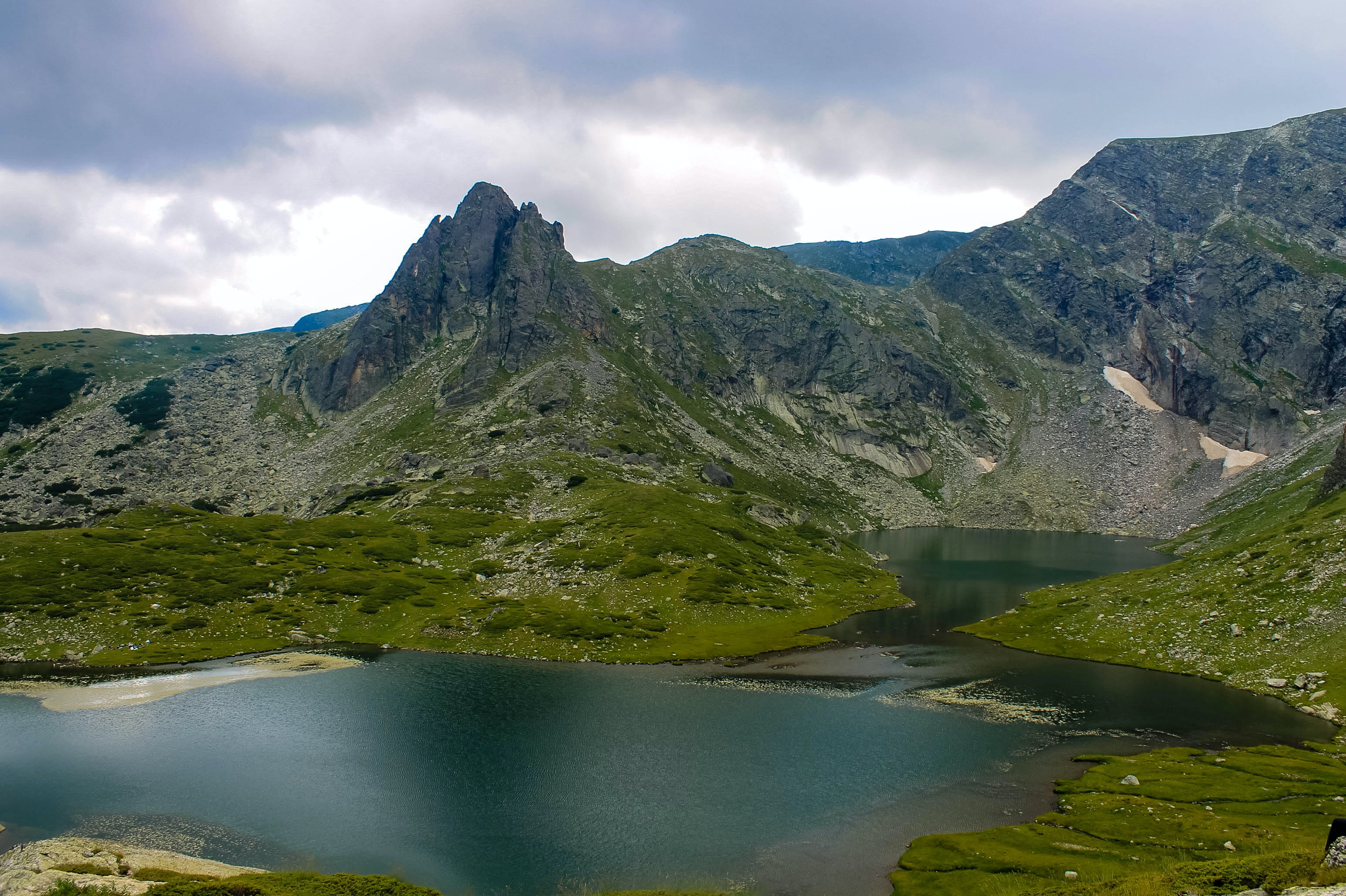 A dark turquoise lake in the middle of a green mountain valley