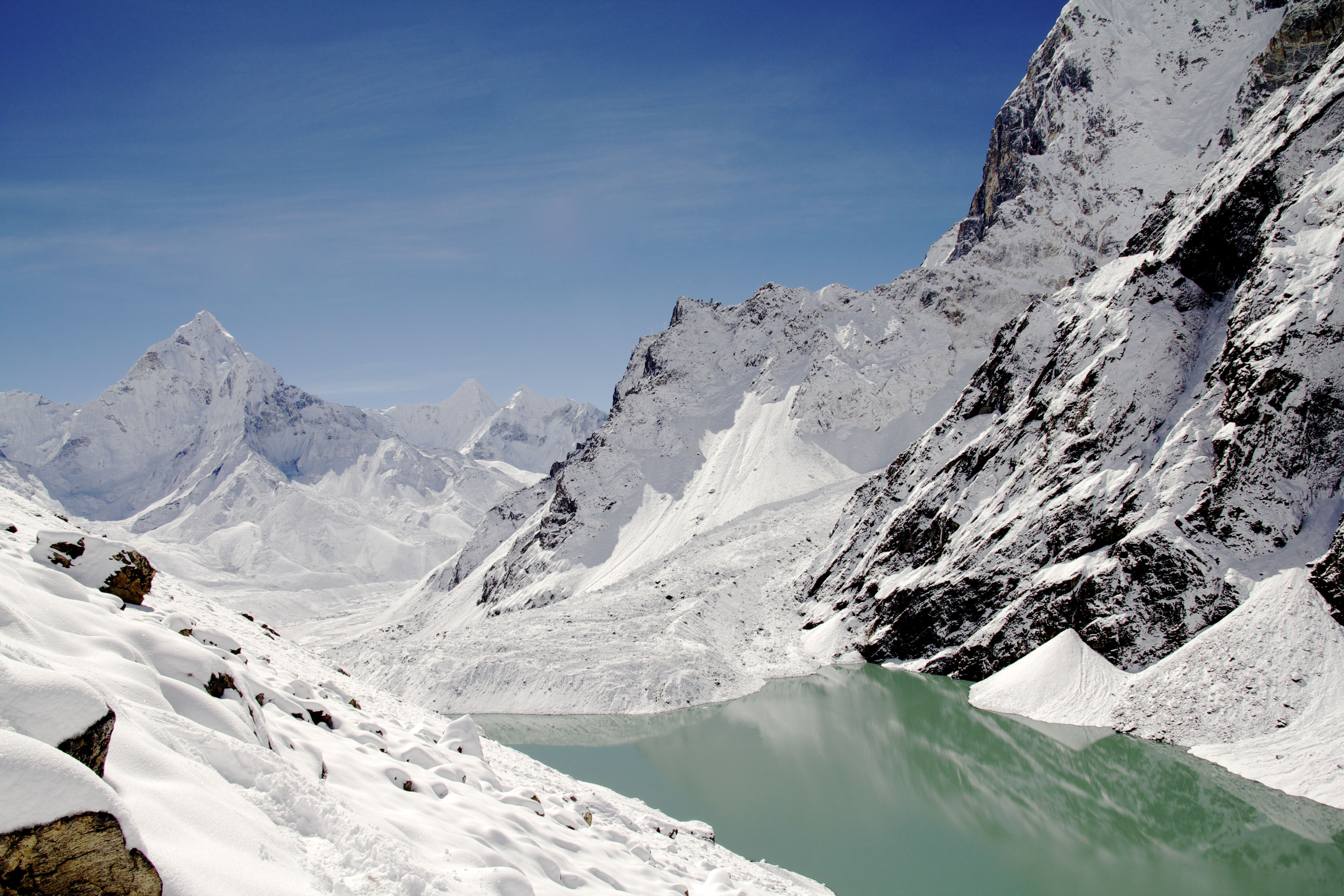 A clear stream running under mountain slopes covered with a thick layer of snow