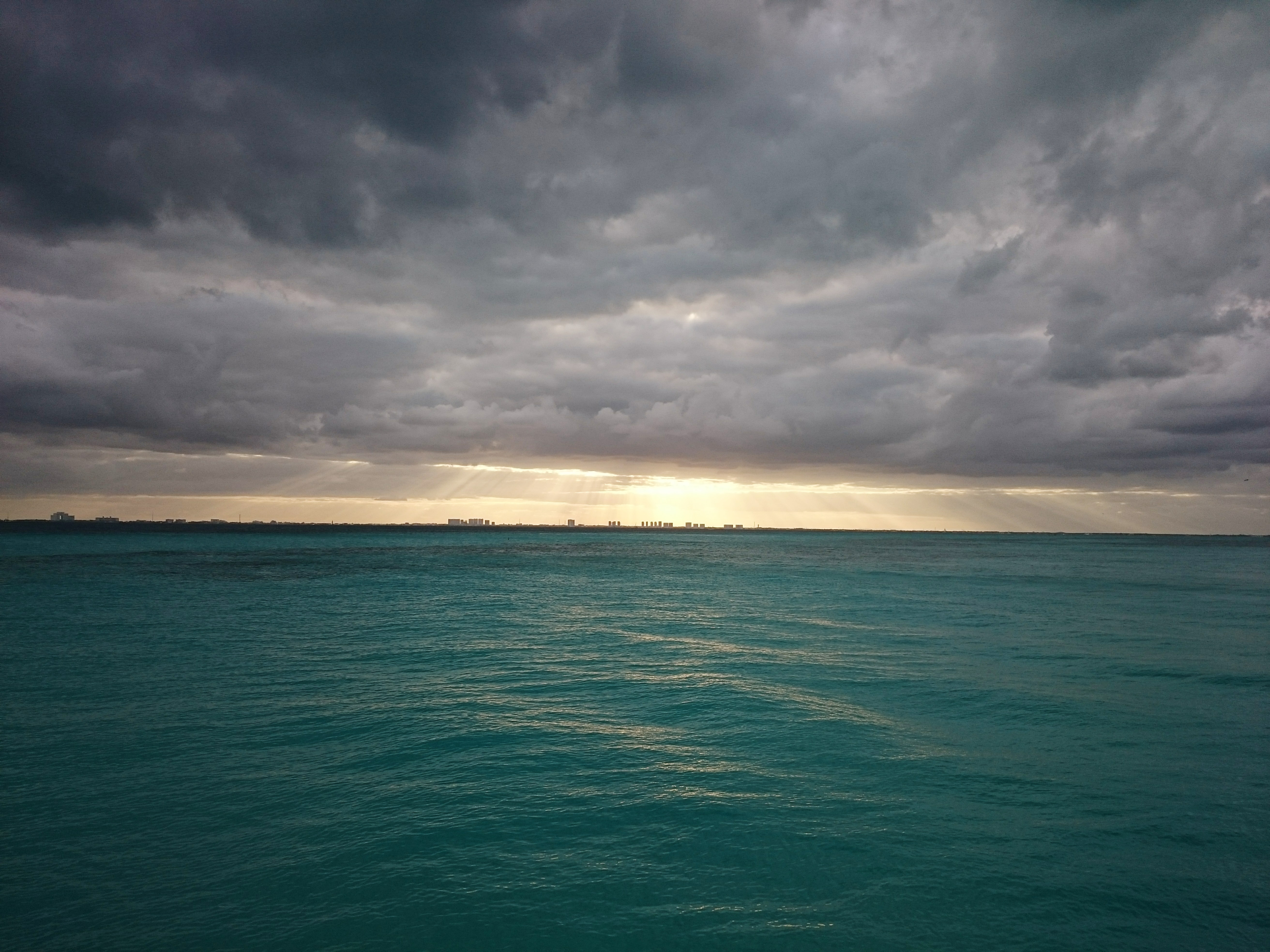 A turquoise sea with a city skyline on the horizon on a cloudy day