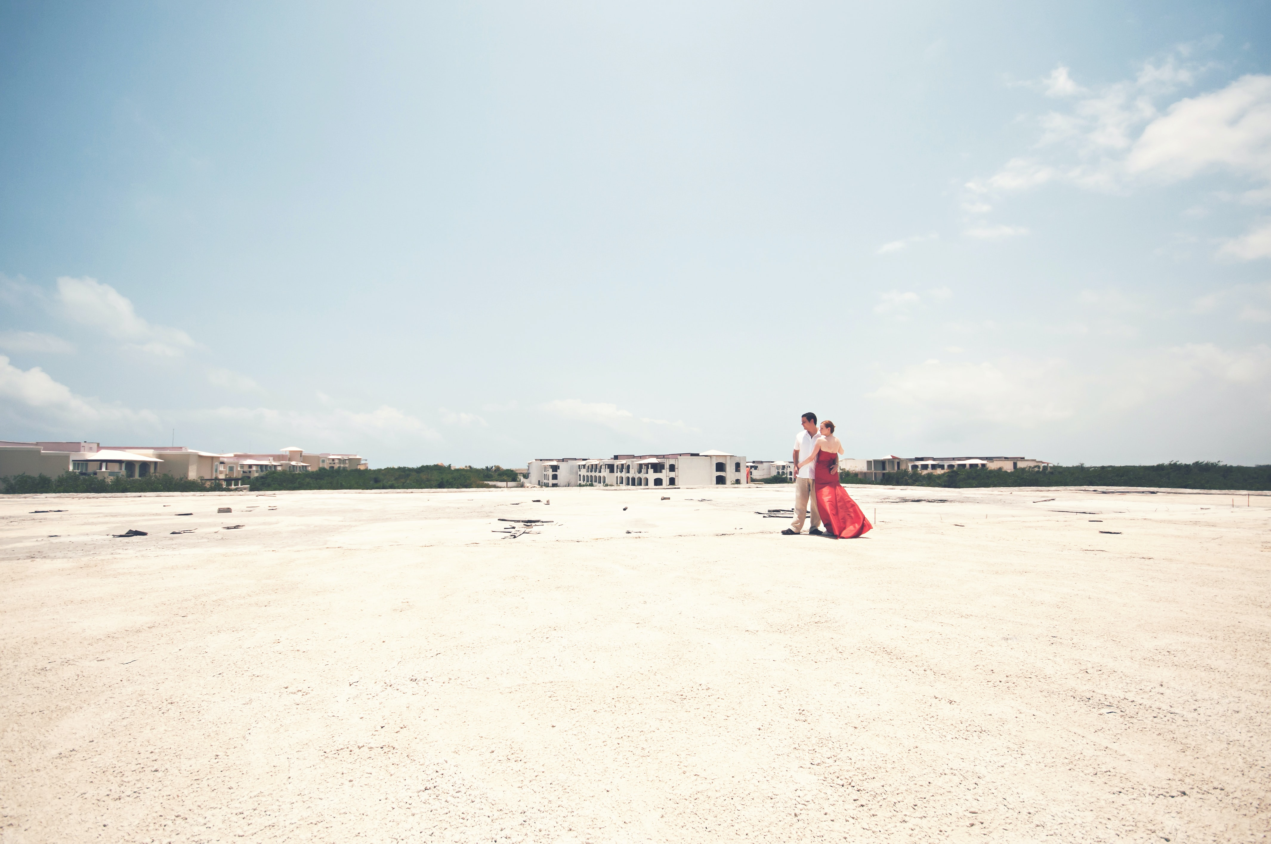 Man in white shirt and a woman in red dress on the sand beach