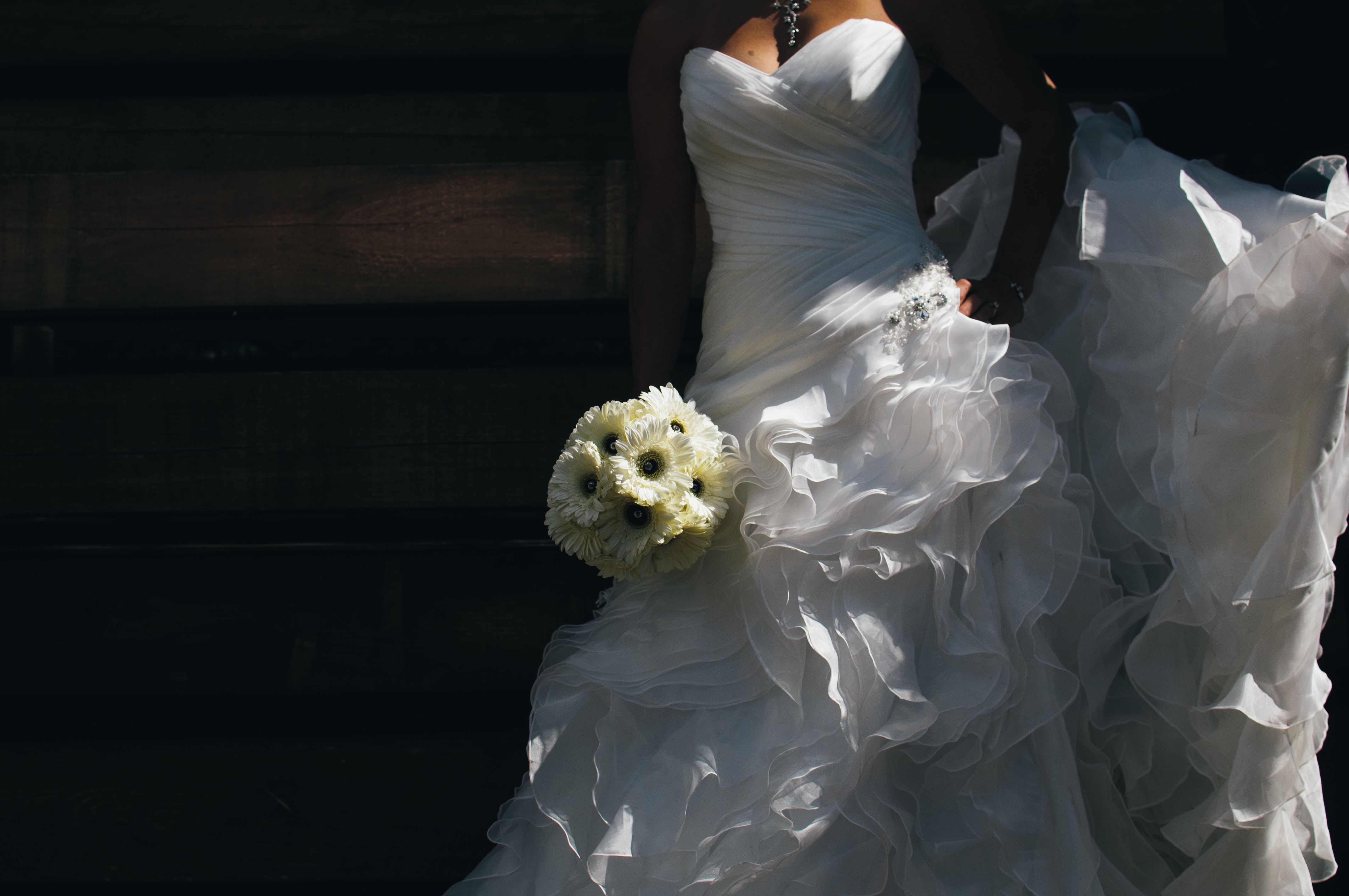 A bride holding her bouquet of daisies wearing a ruffled wedding dress