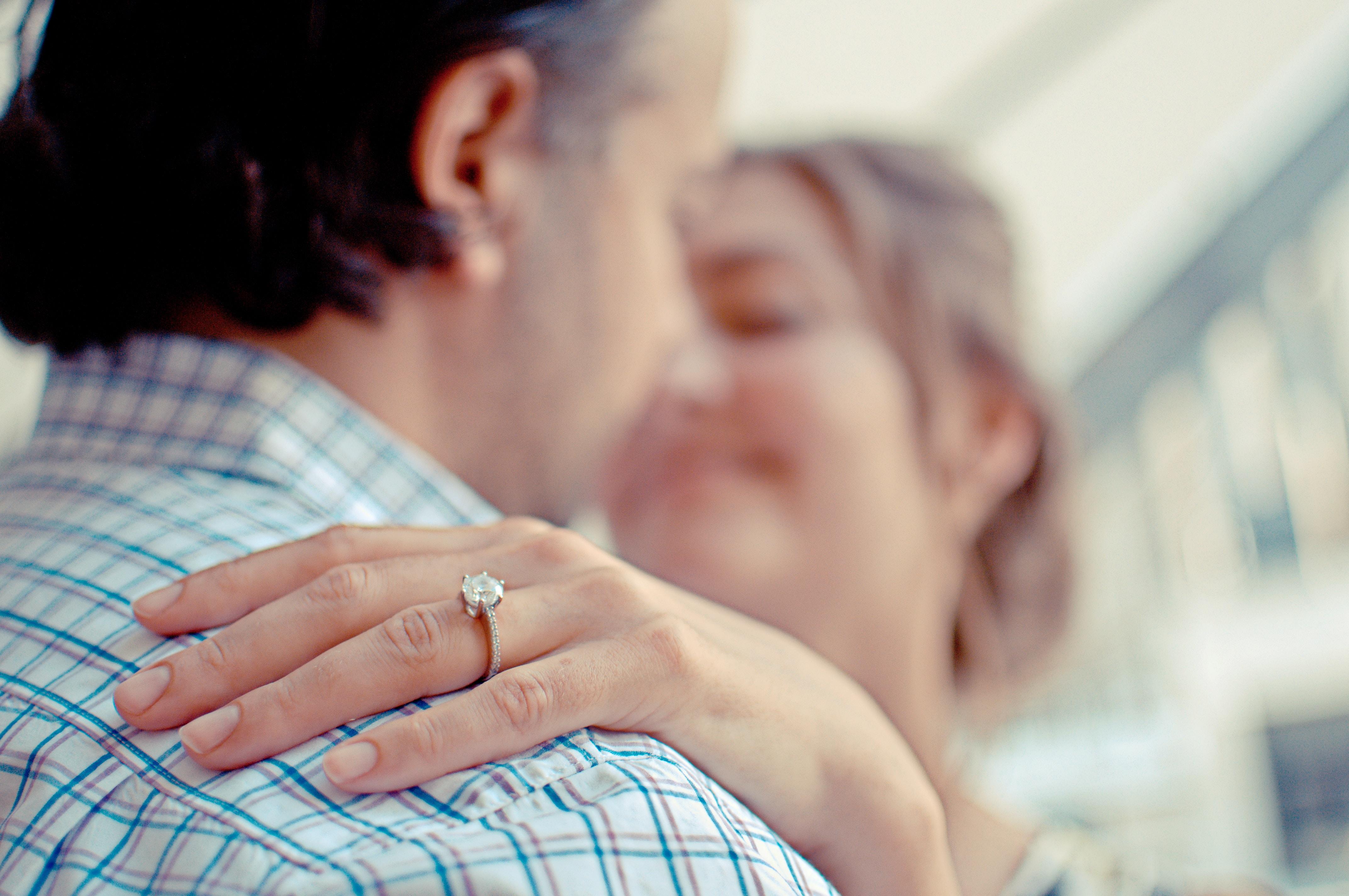 Bride's hand sits on groom's shoulder showing off her wedding ring