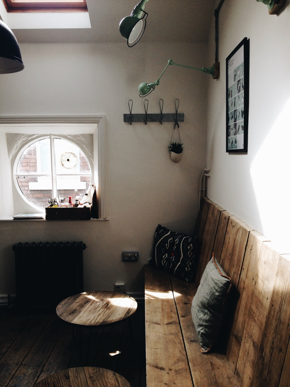 brown wooden bench beside white painted wall