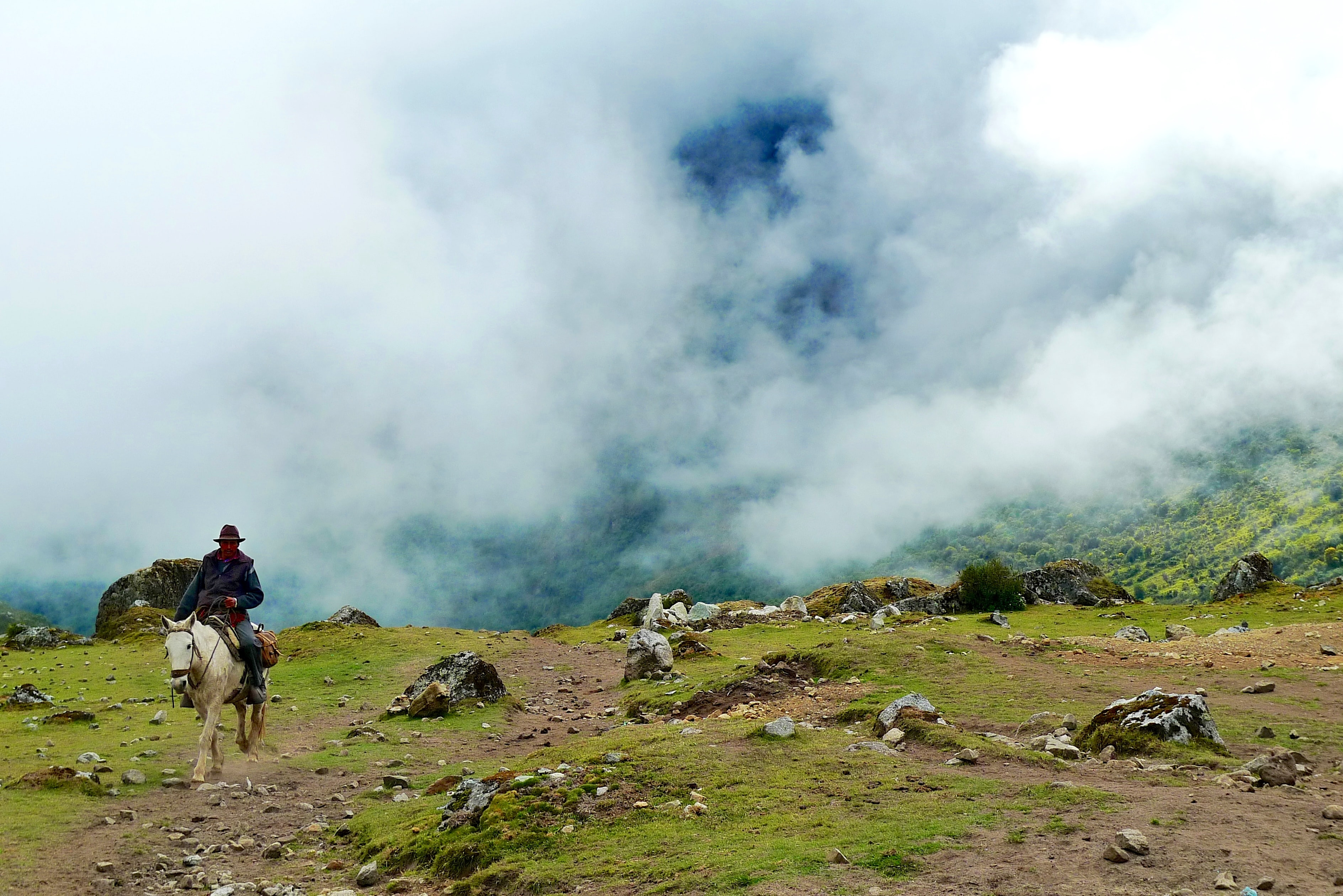 A man in a cowboy hat riding a horse on a rocky slope with mist in the valley behind his back