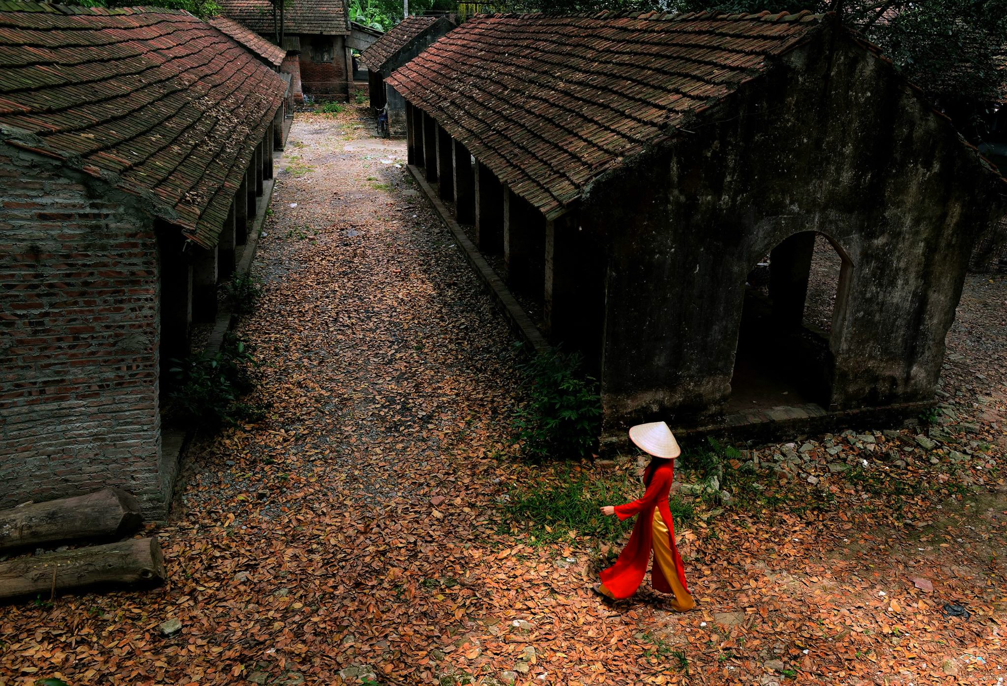 woman walking near abandoned houses