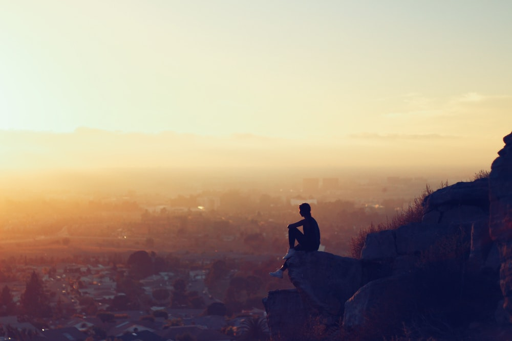 man sitting on rock formation in cliff during golden hours