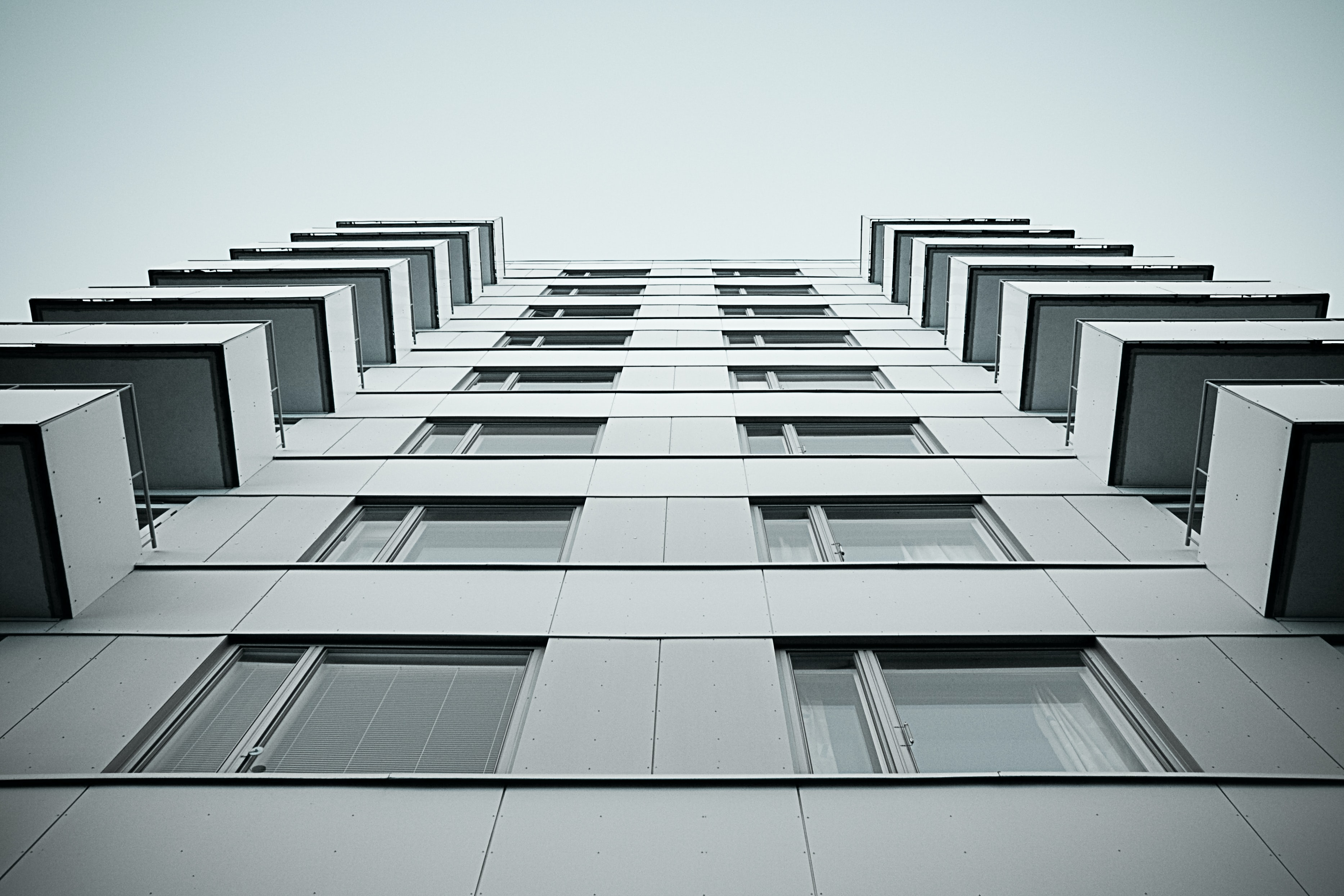 Looking up at gray high rise apartment with balconies and square windows
