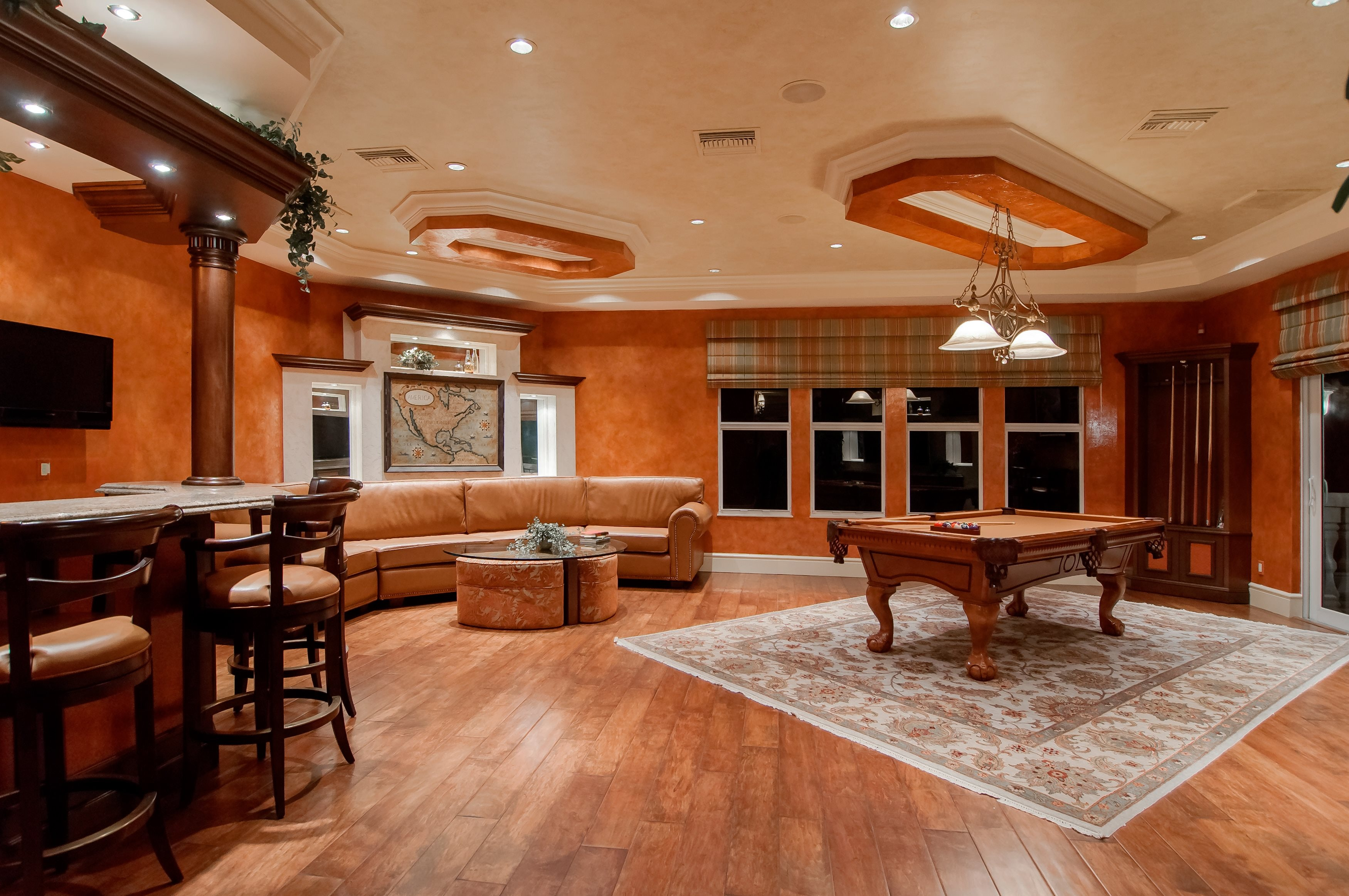 billiard table in center of brown painted room