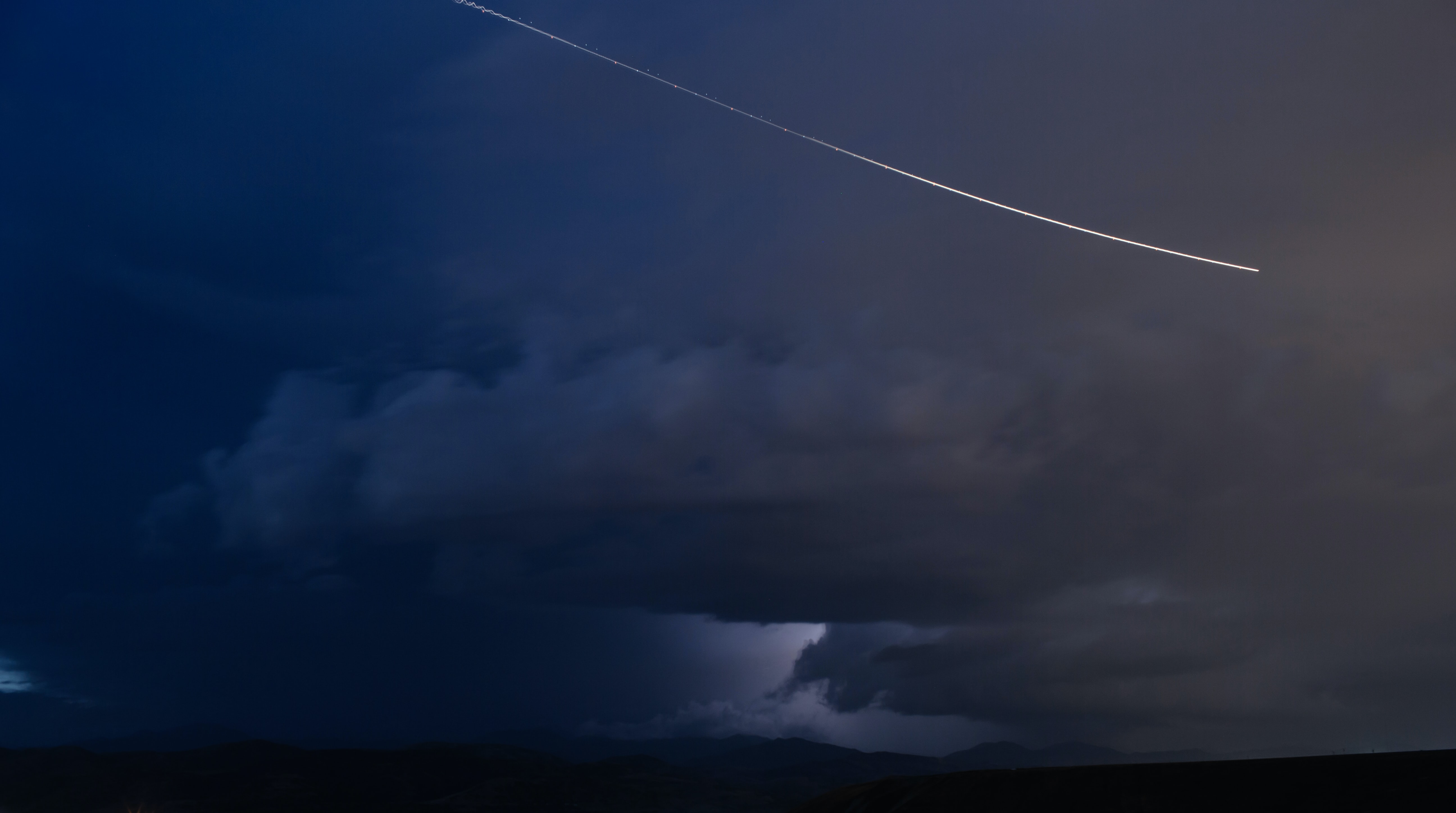 jet flying on sky with dark clouds