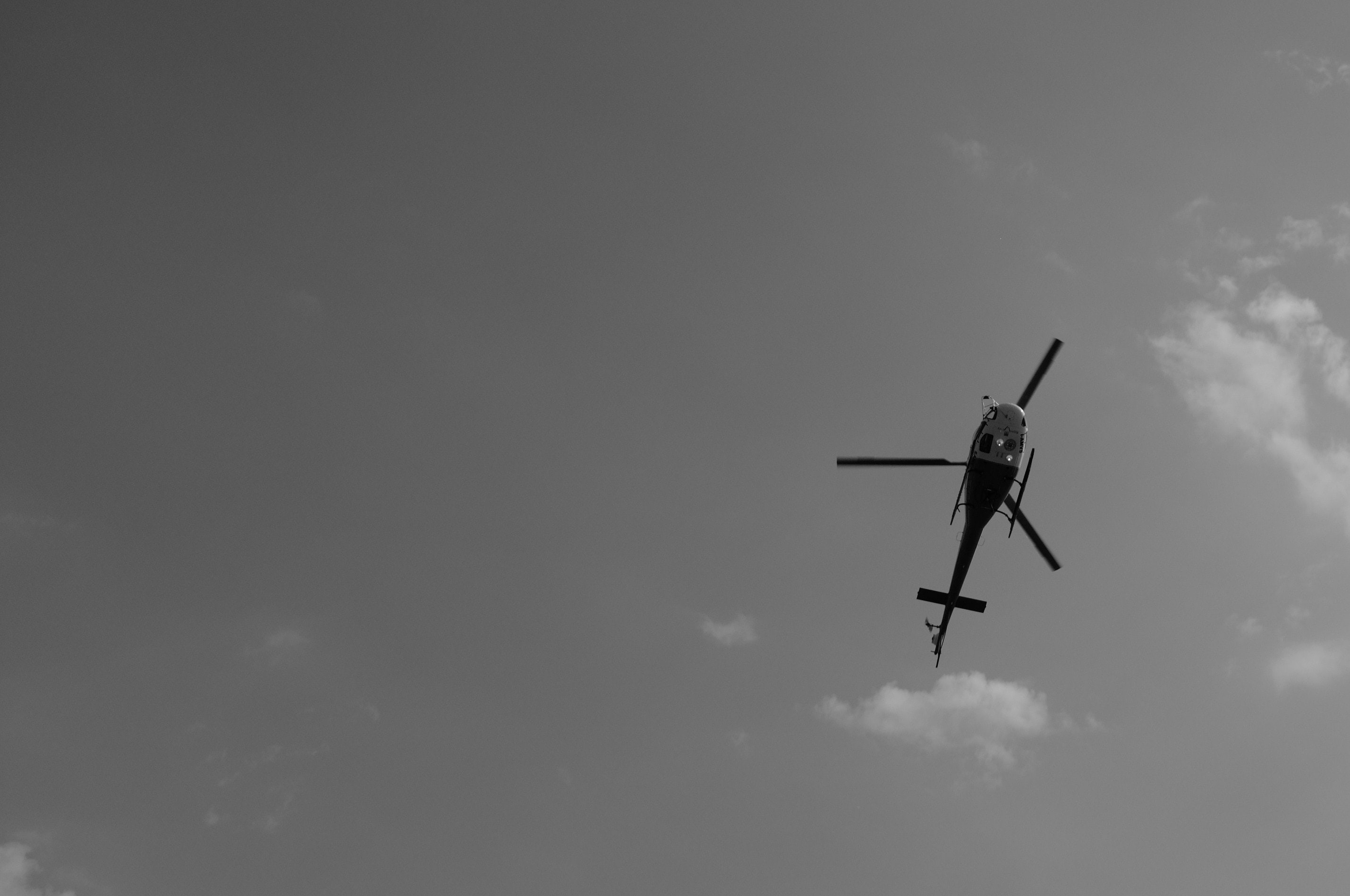 Black and white photo of a helicopter flying overhead.