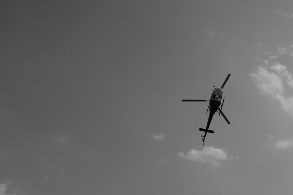 helicopter flying under white clouds