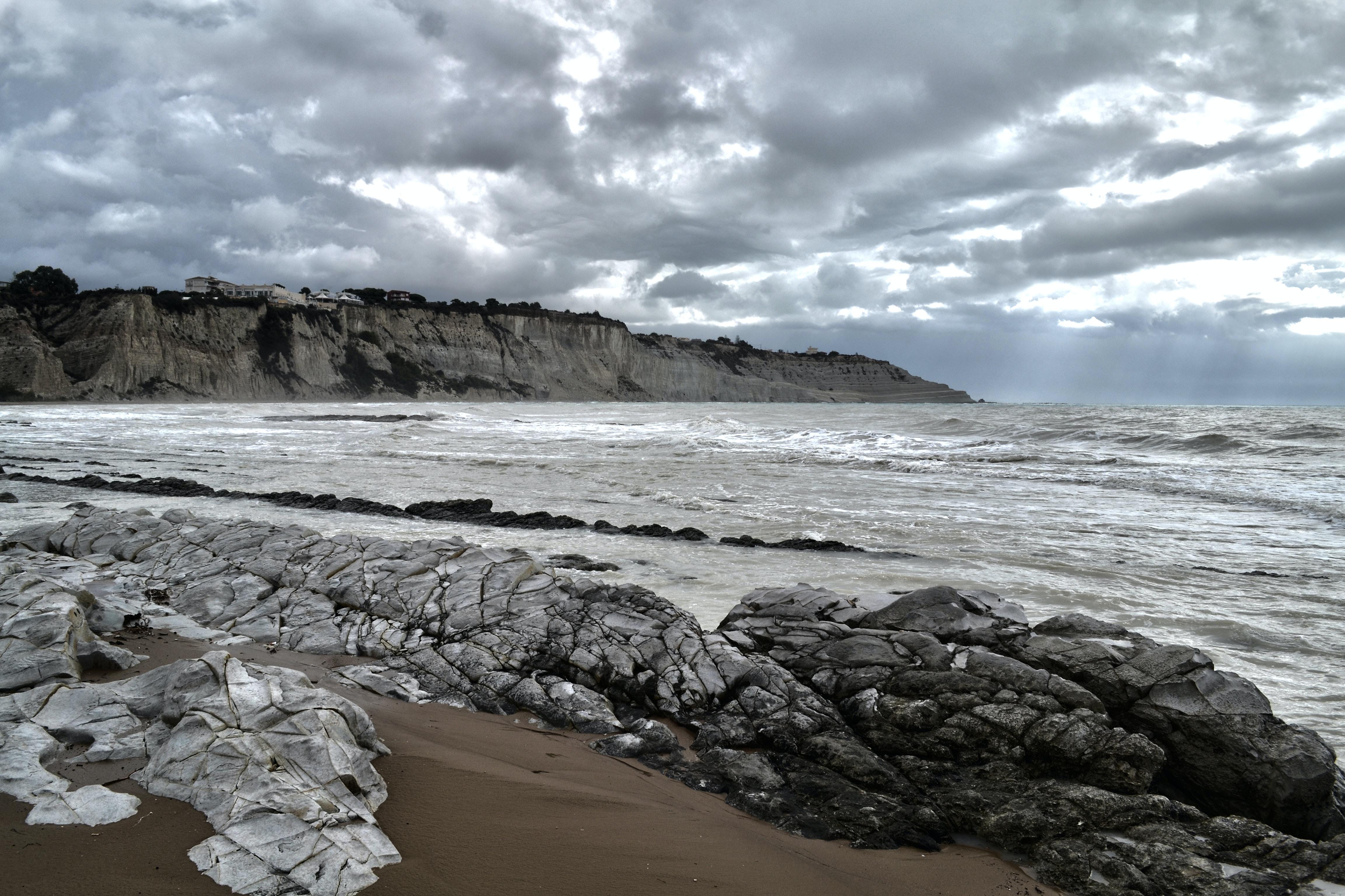 grey rocks near sea under grey sky